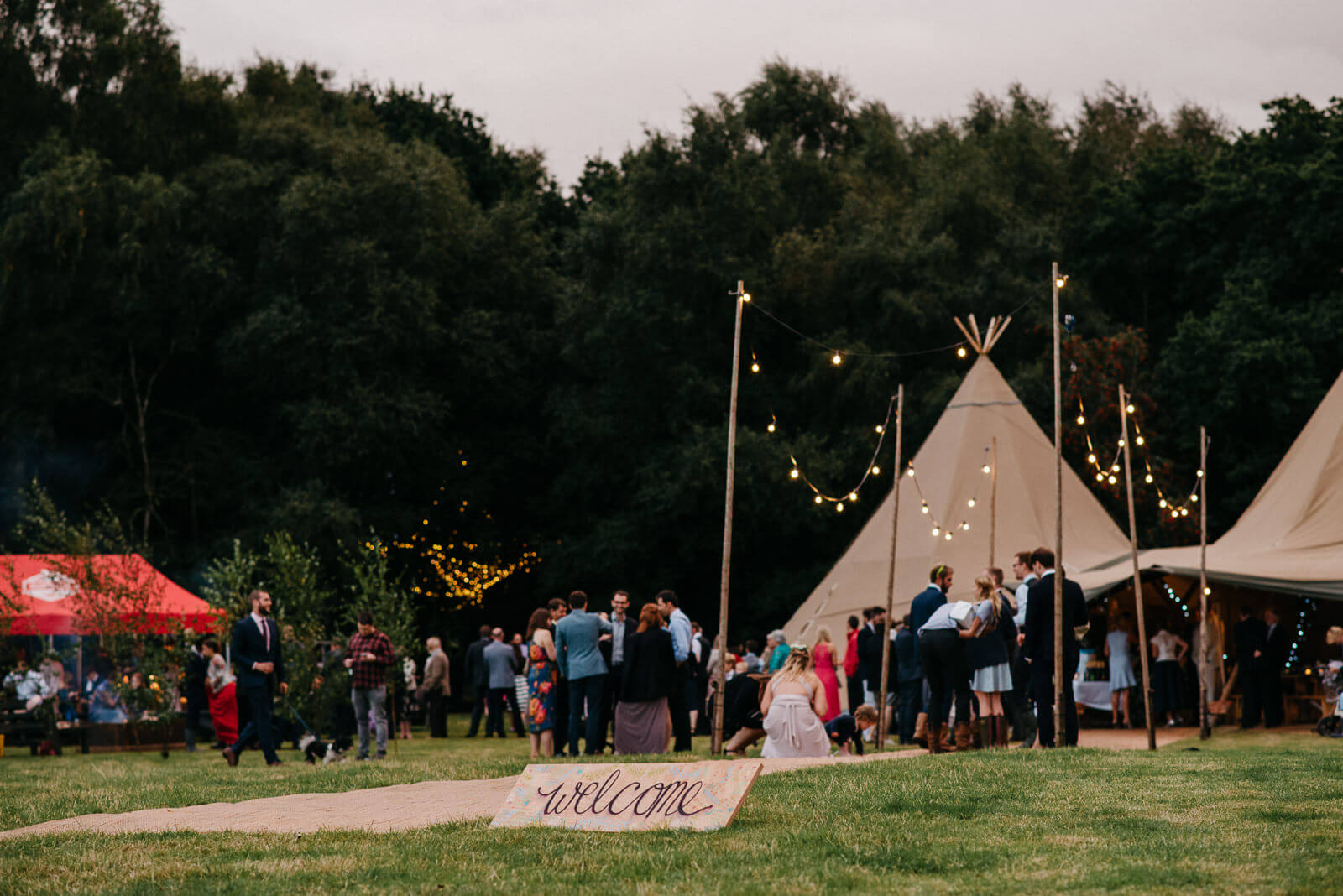 Guests enjoying chatting next to tipi at Shropshire festival style wedding