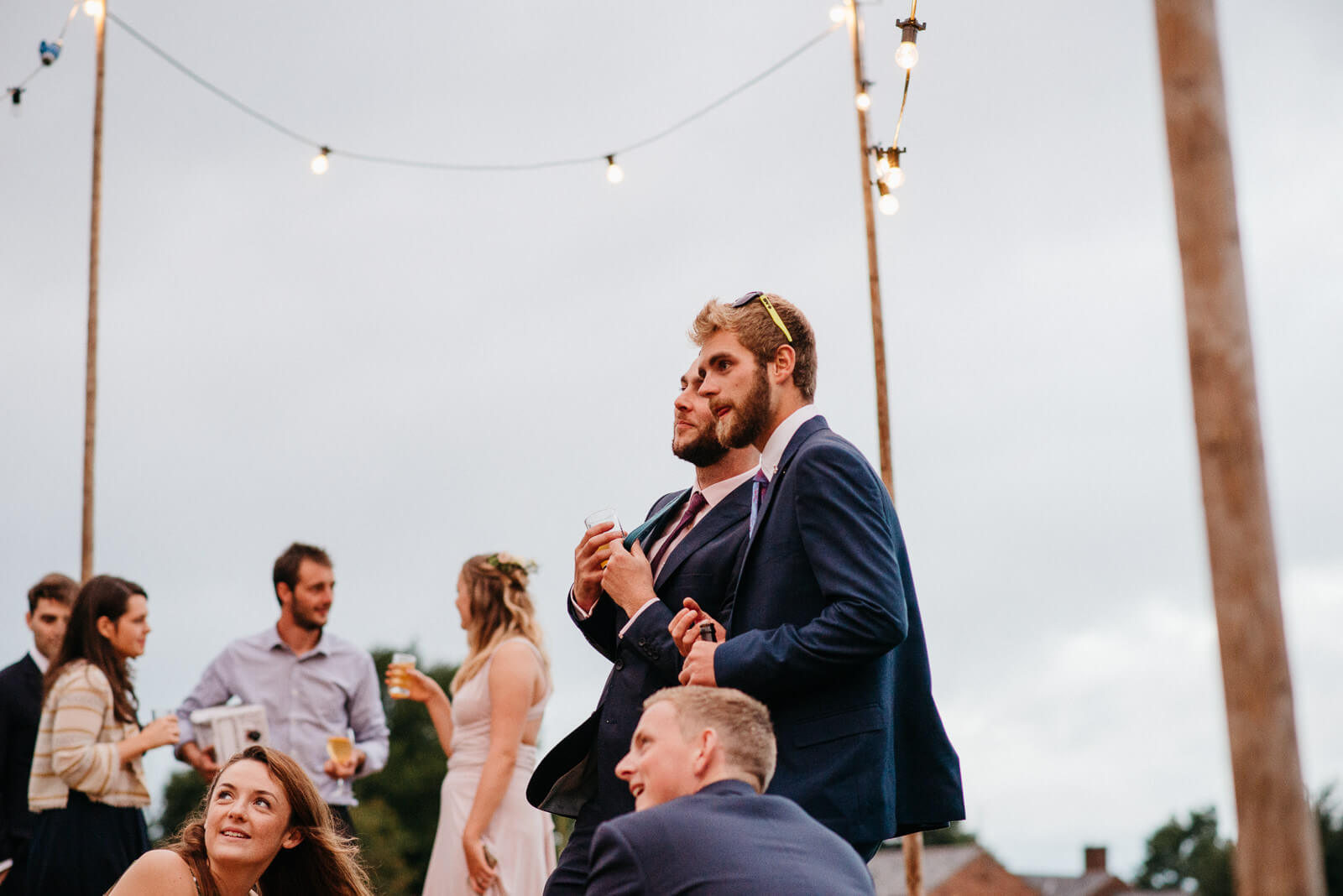 Wedding guests look on under festoon lighting at Shropshire festival wedding