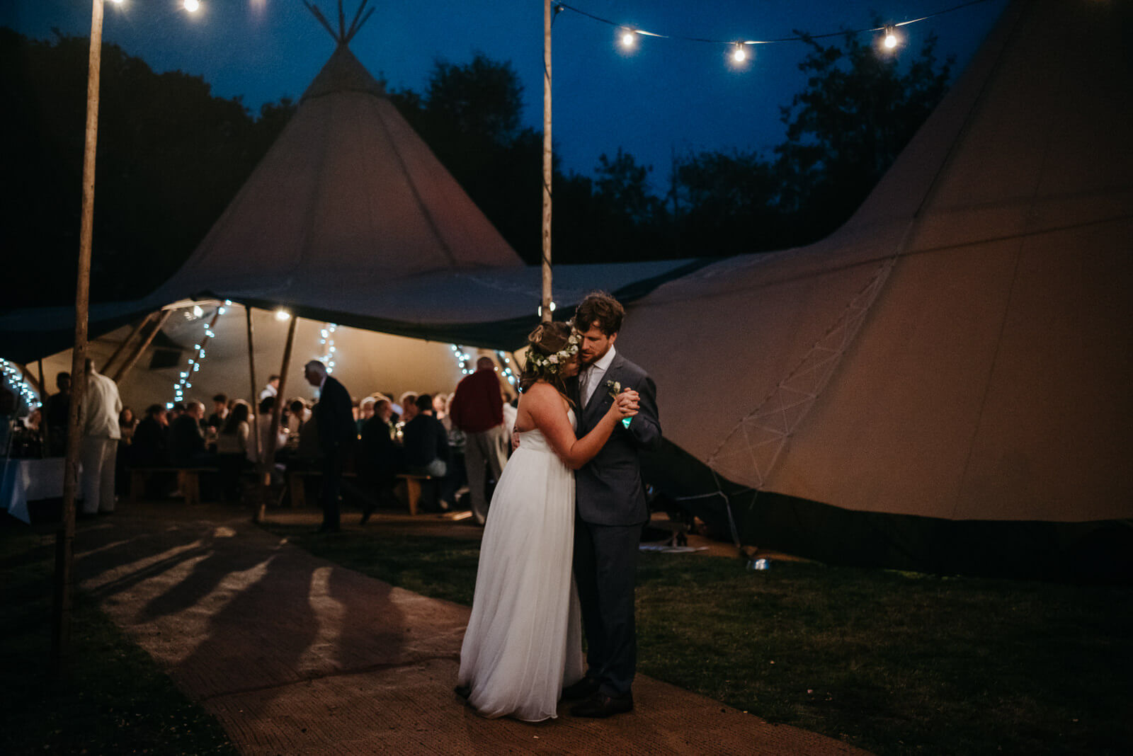 Bride and groom dancing in darkness with light coming from tipi and festoon lighting