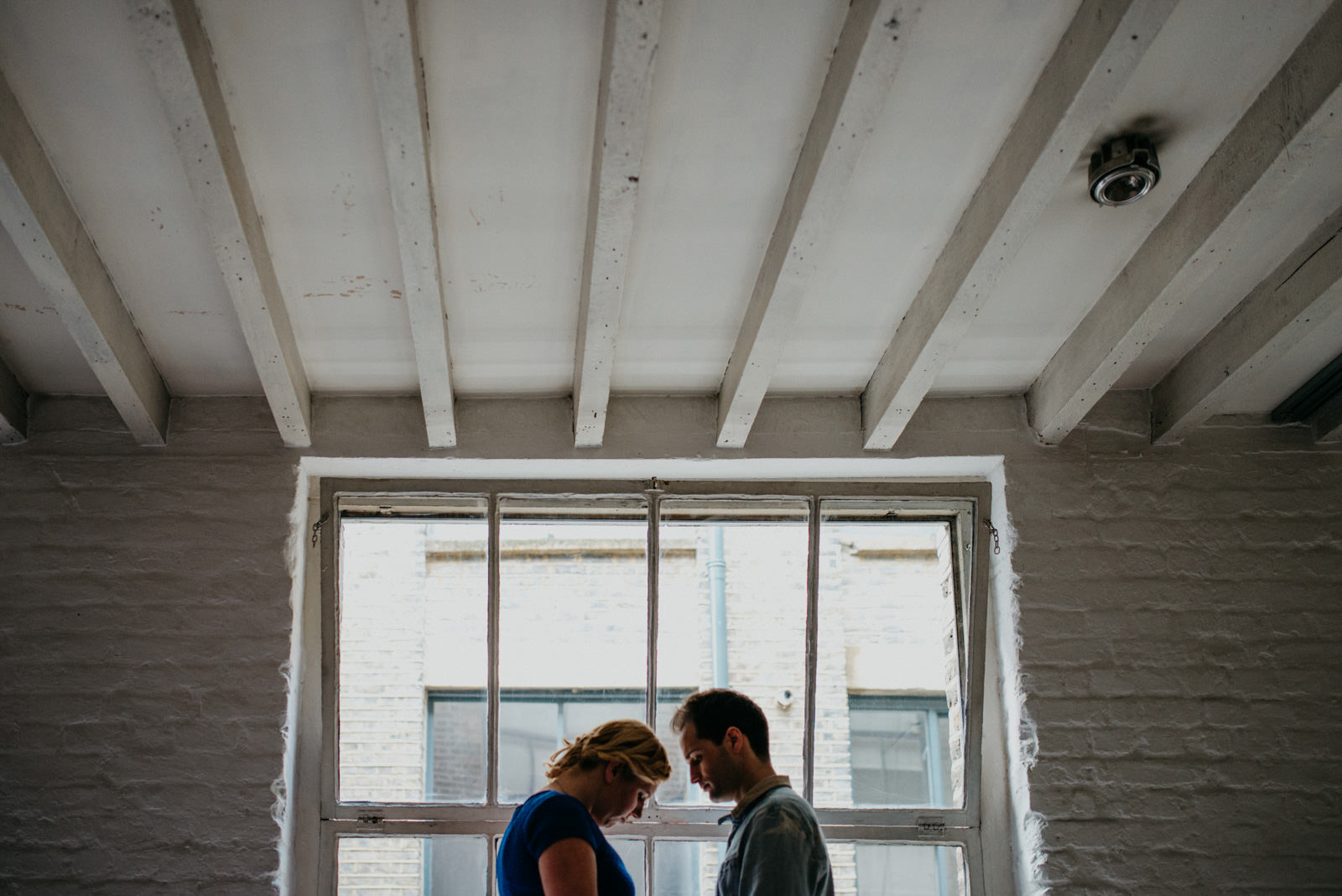London Couple standing in front of factory window during their Shoreditch couple shoot