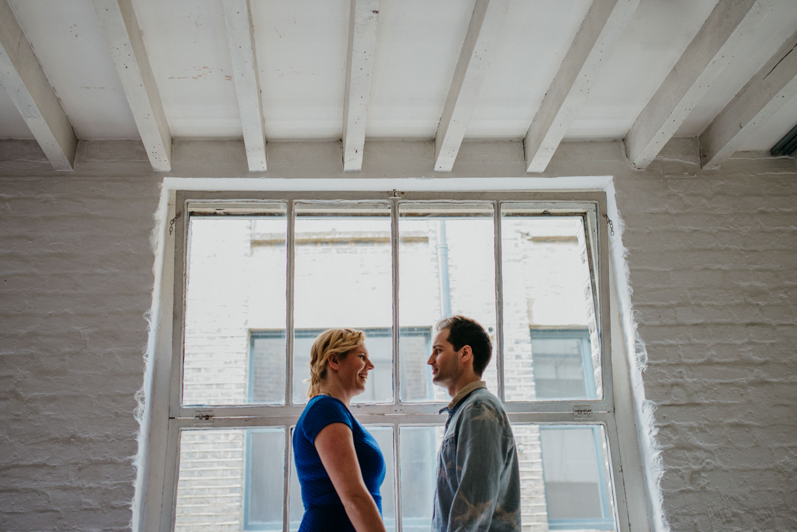 Shoreditch couple in front of factory window during East London couple shoot