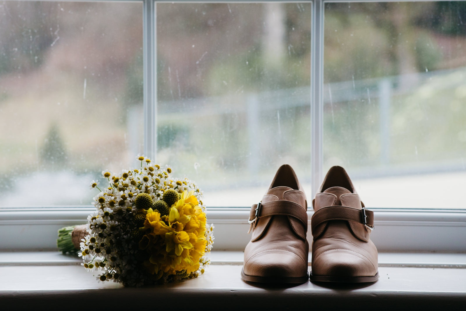 Brides wedding shoes and & bouquet on window ledge at New House Hotel in Lisvane