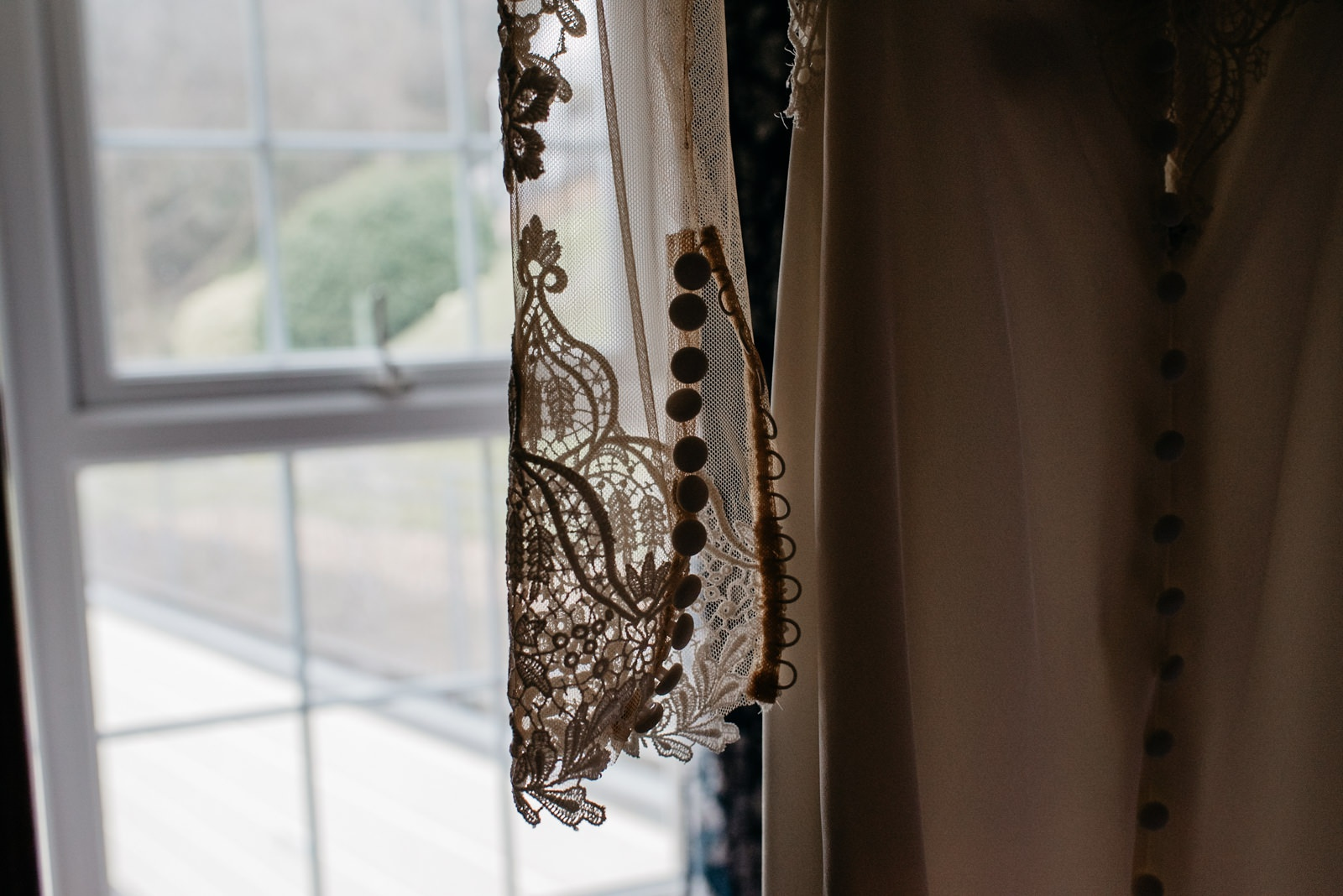 fine art photograph of brides lace wedding dress hanging in New House Hotel in Lisvane
