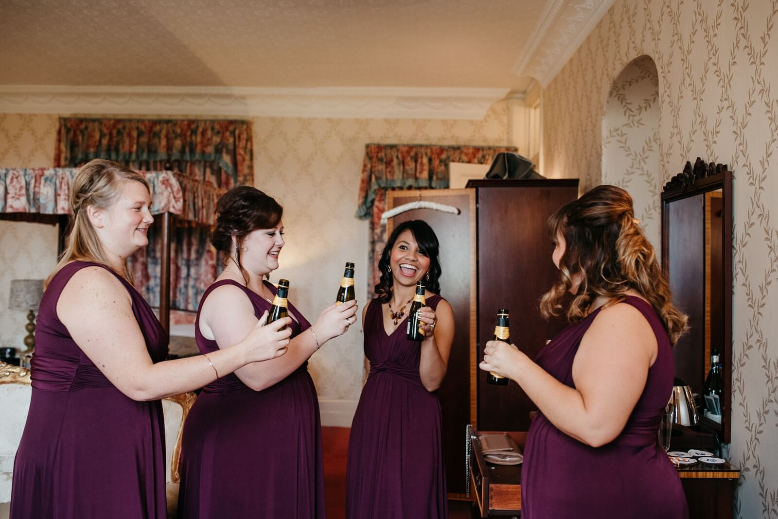 Bridesmaids in wine dresses sharing a toast at Cardiff New House Hotel
