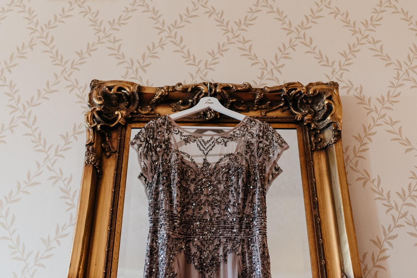 Brides sequinned 'Phase Eight' dress hanging on gilded mirror at New House Hotel, Cardiff