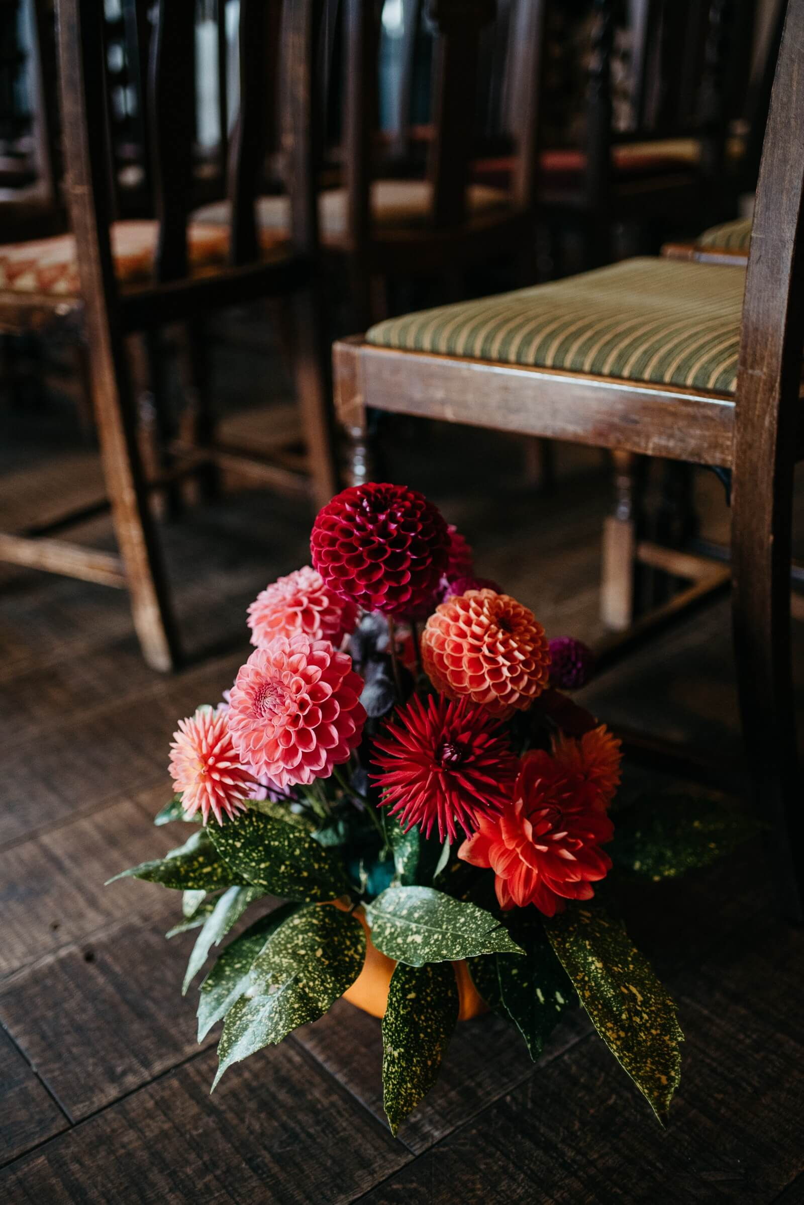 Floral arrangement of dahlias in scooped out pumpkin at alternative halloween wedding