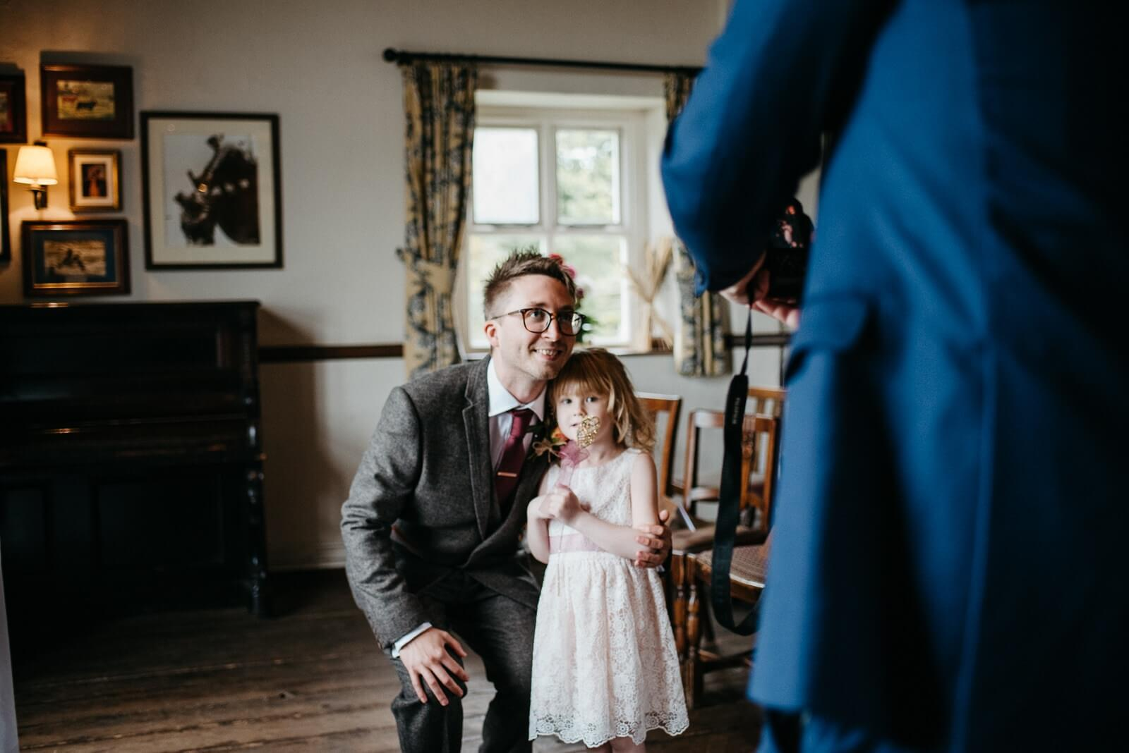 Groom poses with flower girl ahead of the wedding ceremony at Ty Mawr