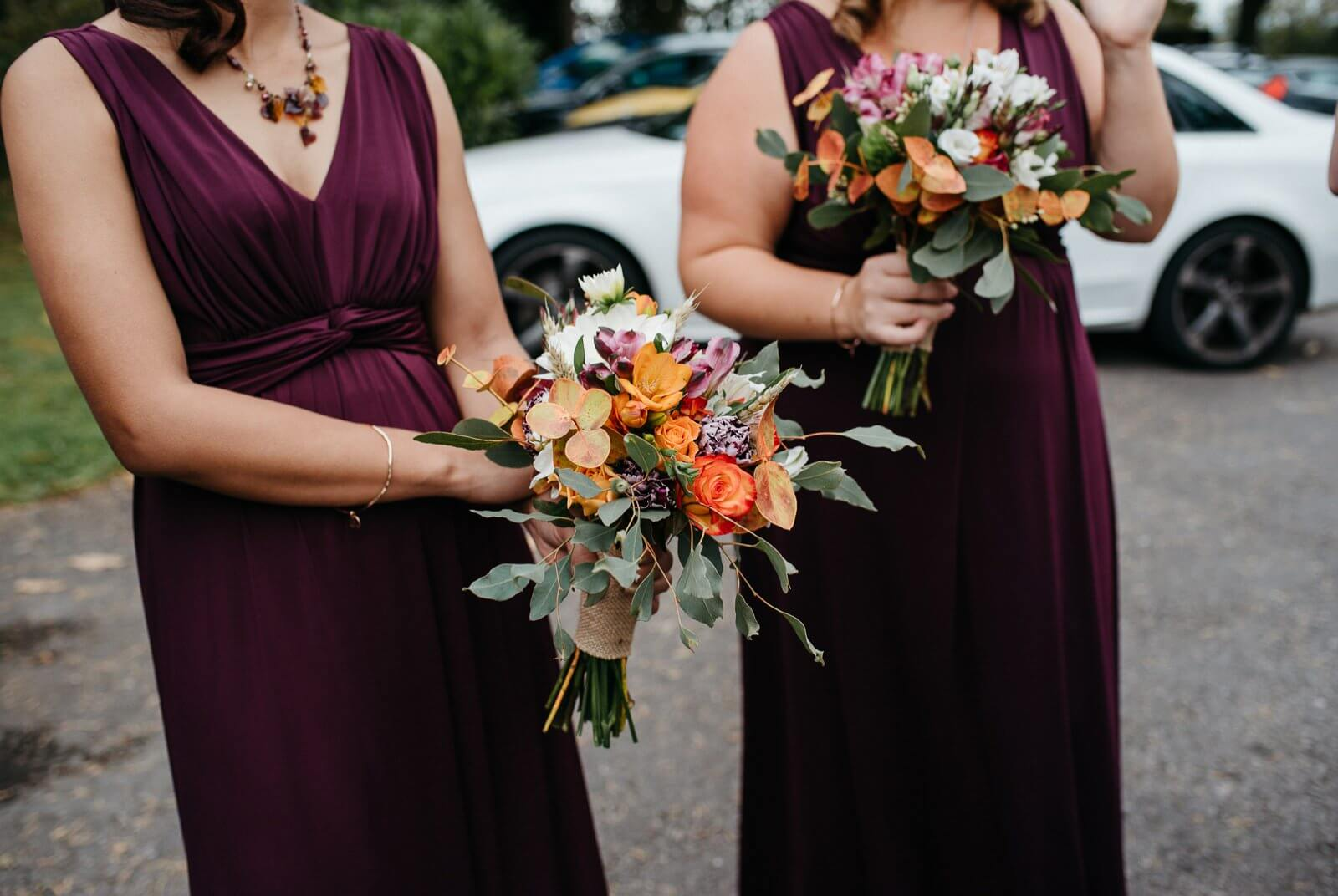 Autumnal bridesmaids wearing wine burgundy maxi dresses clutch onto gold, orange and hot pink bouquets outside Cardiff wedding venue