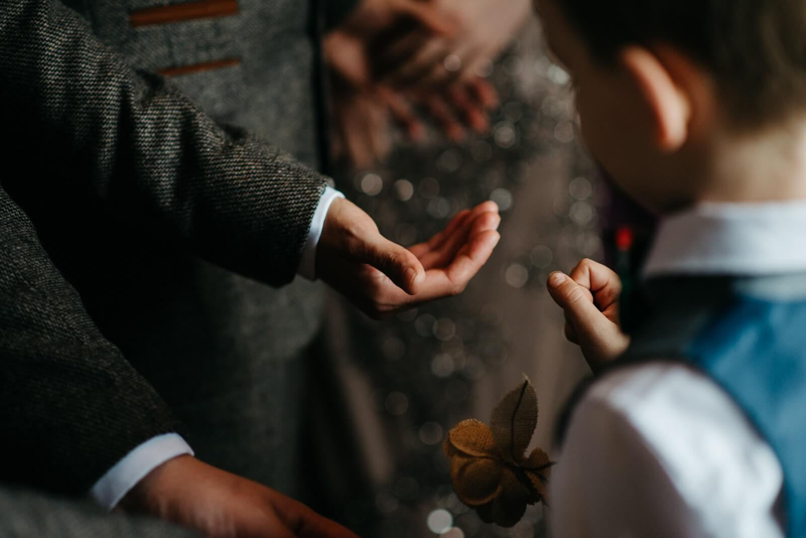 Small groomsmen pageboy handing the groom the wedding bands during their Cardiff wedding ceremony at Ty Mawr