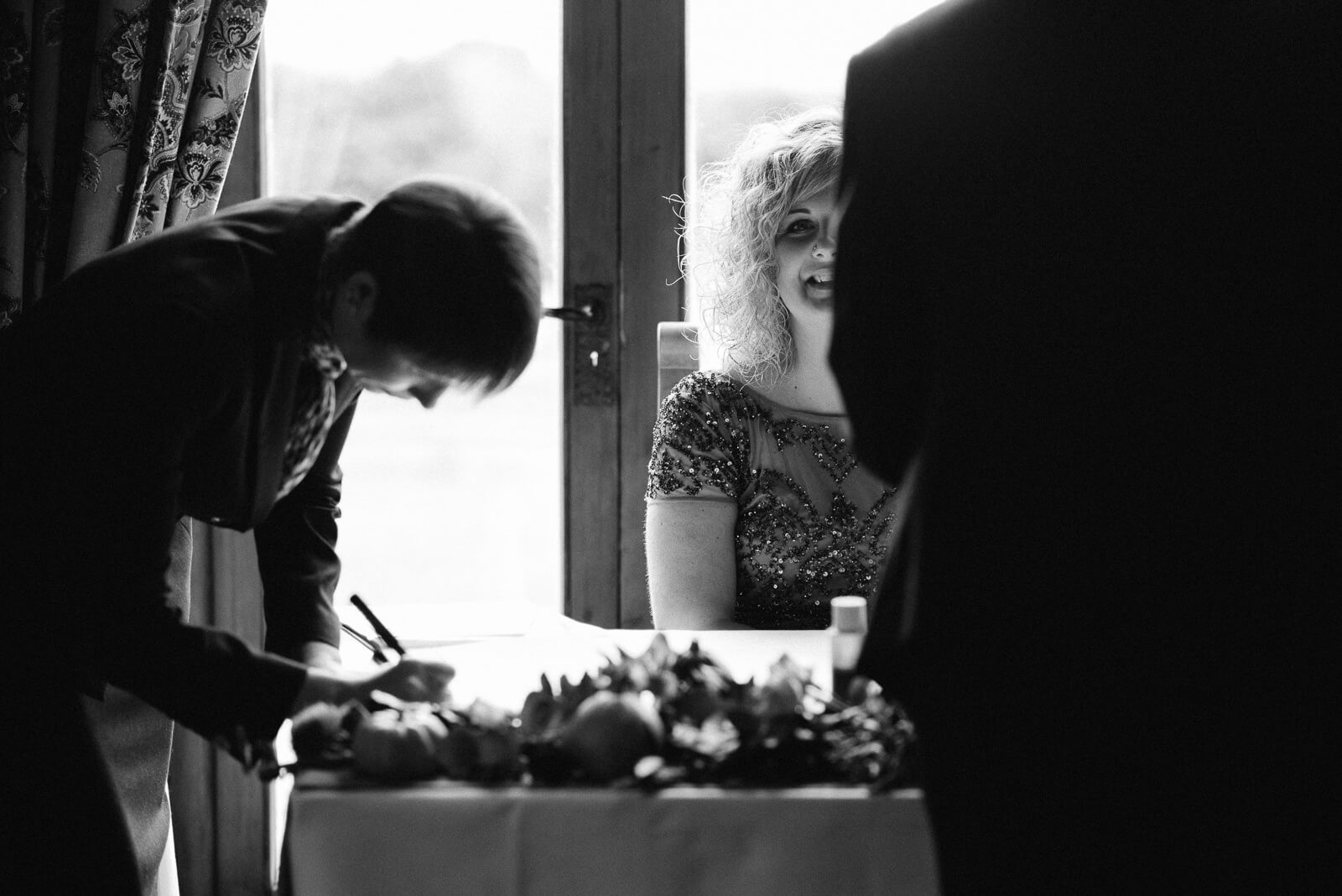 Black and white photography of happy bride following the signing of the register at Ty Mawr, Cardiff