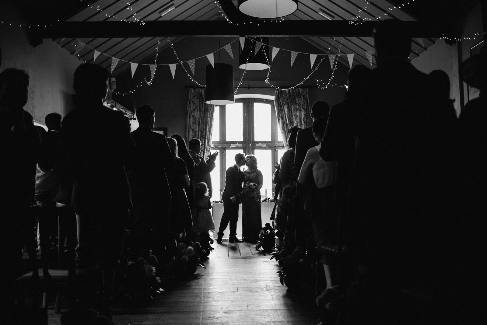 Moody black and white photograph of bride and groom sharing a kiss before walking back down the aisle at Cardiff wedding