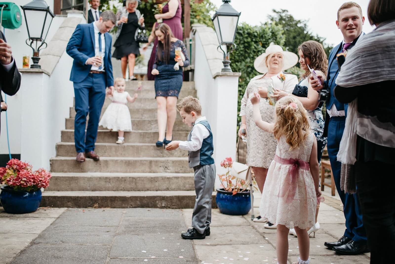 Small groomsman playing with confetti before bride and grooms entrance at Cardiff wedding