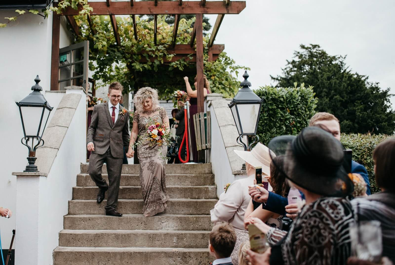 Bride and groom walking down steps following their welsh wedding ceremony at Ty Mawr