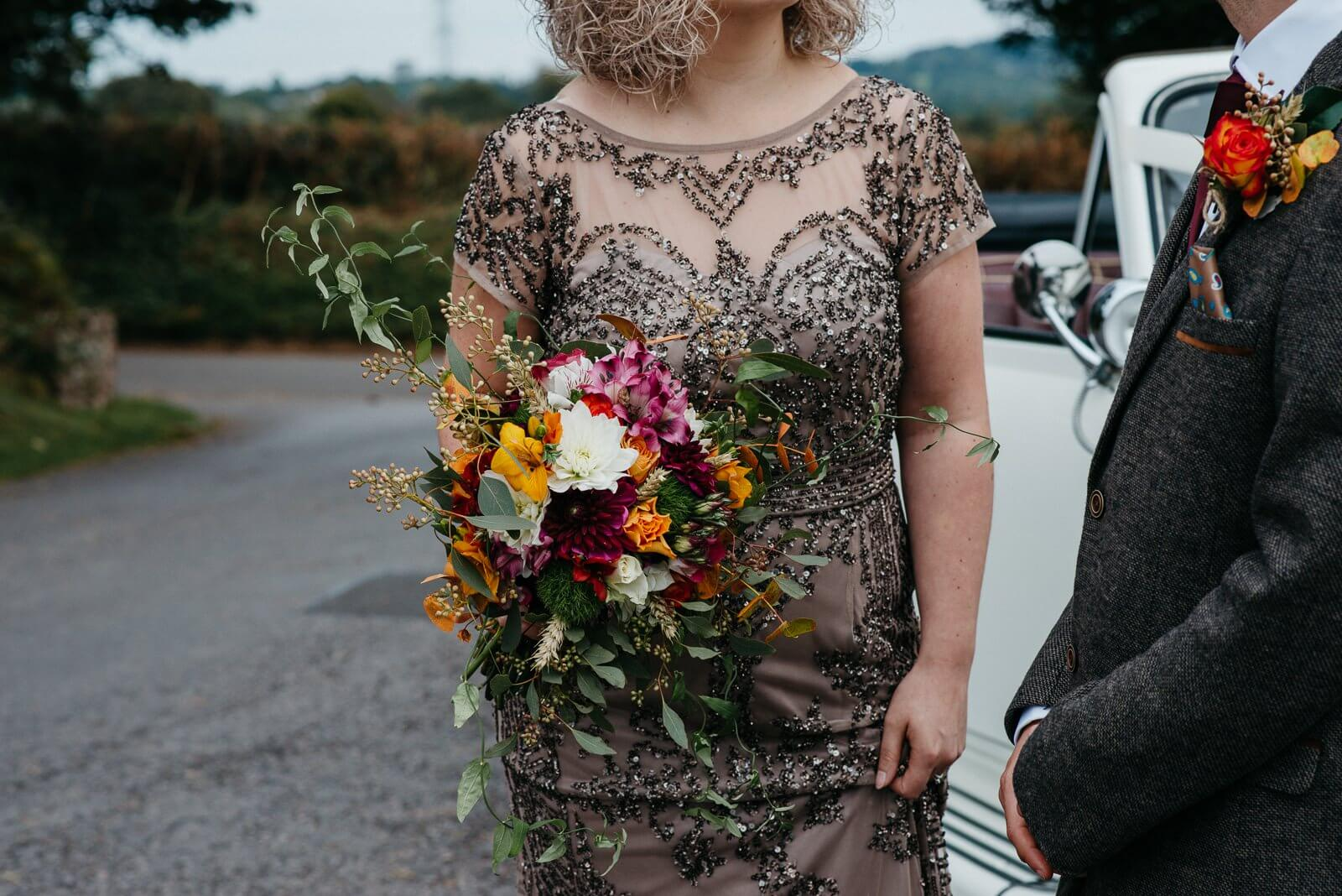 Candid bride in stylish sequinned evening gown holding rustic bouquet of golds and hot pinks while chatting to groom at Ty Mawr wedding, Cardiff