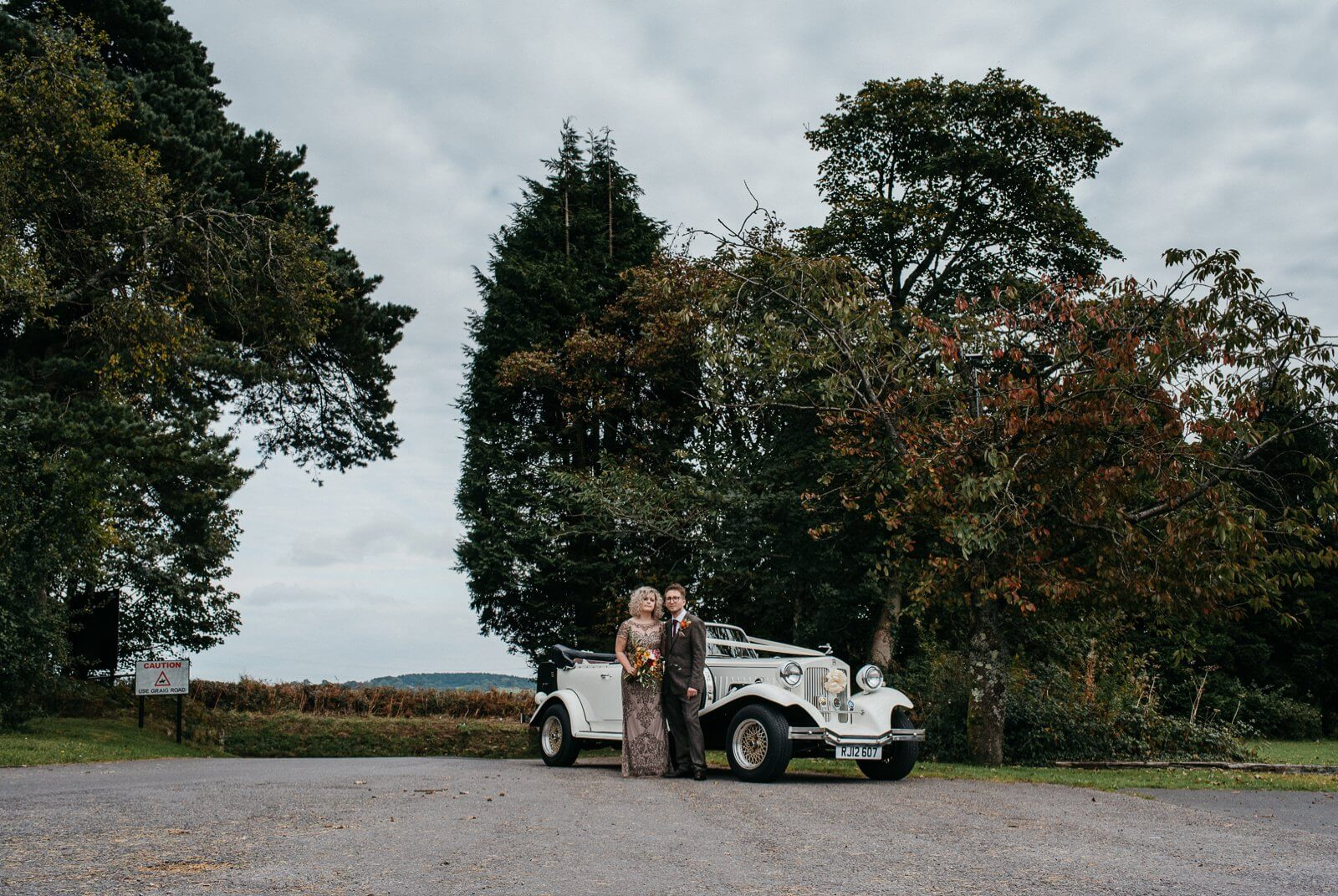 Alternative bride and groom in front of classic wedding car at autumn Cardiff wedding