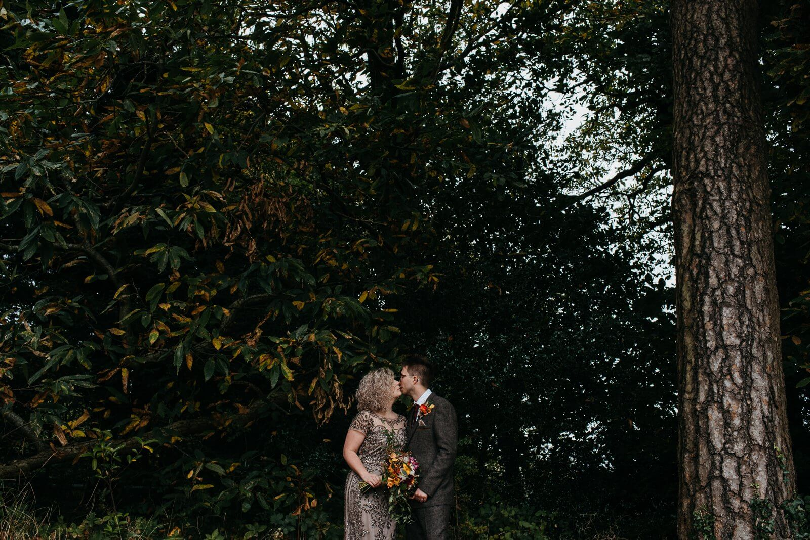 bride and groom kiss on the edge of Cardiff woodland at their alternative Ty Mawr wedding