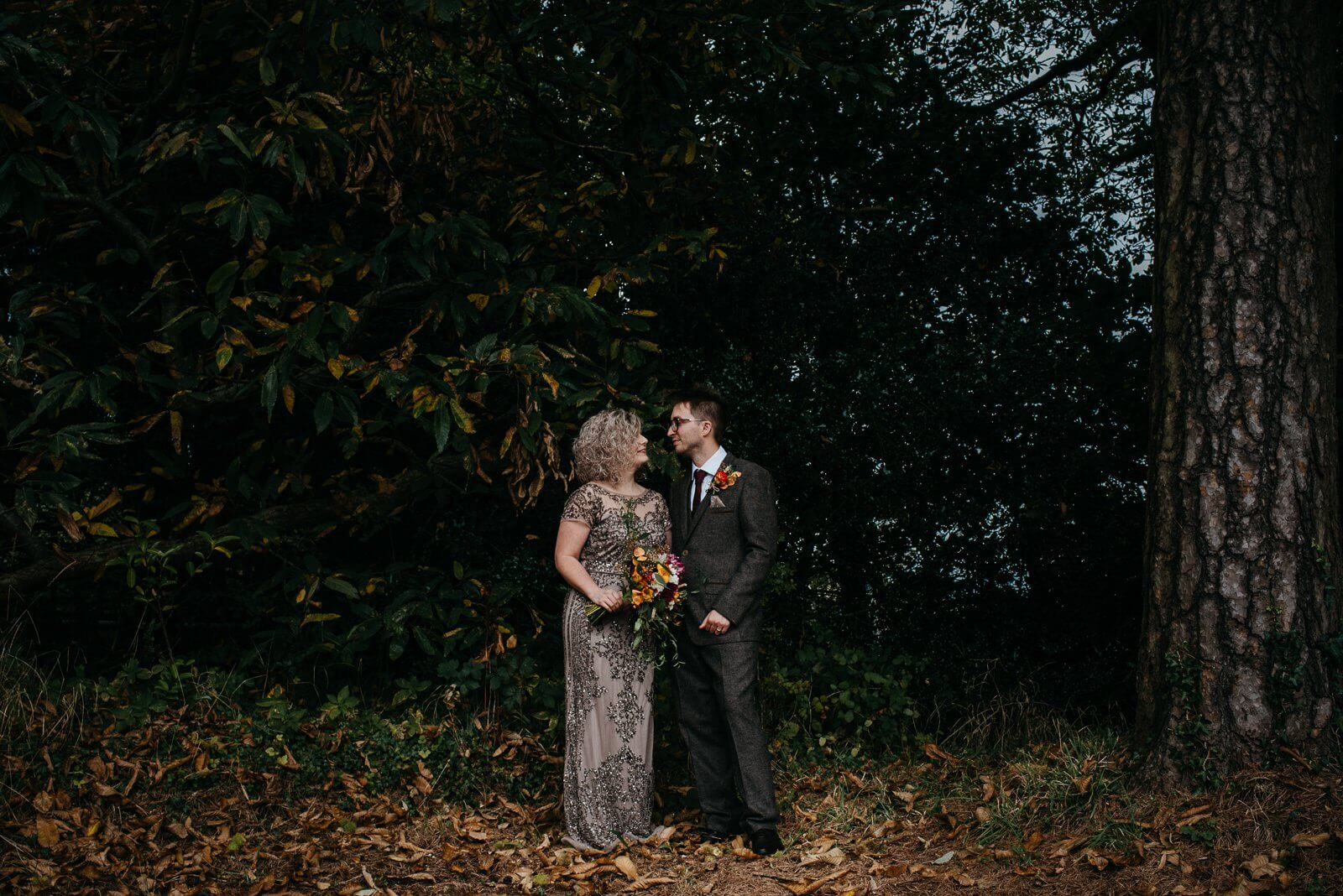 Relaxed photograph of cardiff bride and groom on the edge of the woodland at their autumn halloween alternative wedding