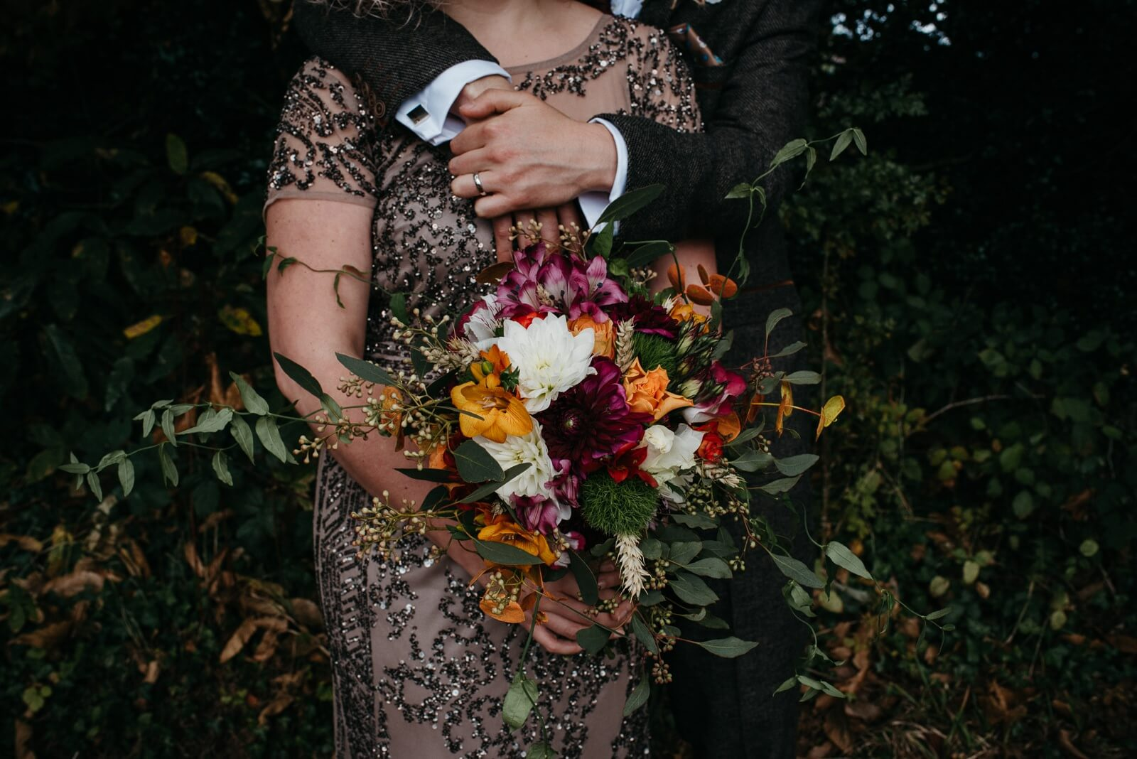 moody photograph of Bride wearing unique sequinned evening gown and groom in woodland holding onto autumnal bouquet