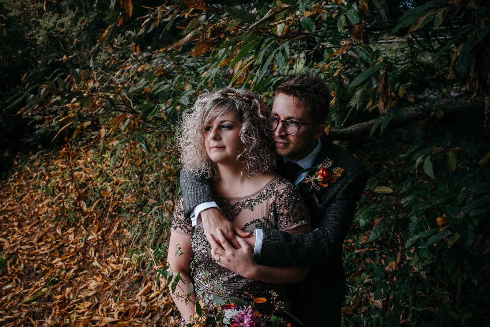 Moody photography of bride wearing unique sequinned dress and room in autumn forest setting for welsh wedding