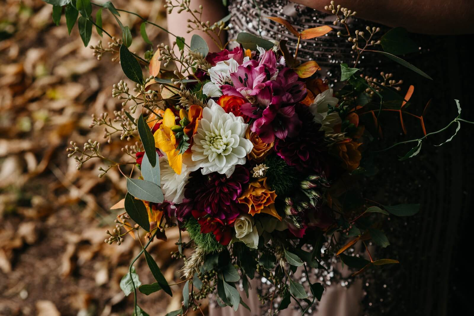 Autumn rustic bouquet of white dahlias, orange and red roses, hot pink dahlias, freesia, foliage and lilies for rustic alternative barn wedding near cardiff