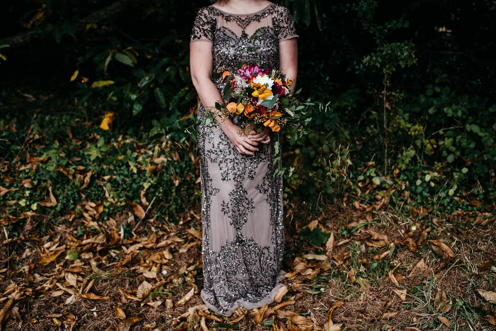 Alternative bride details featuring mink sequinned dress and rustic autumn bouquet of yellow, orange, and hot pink flowers standing in bed of autumn leaves at Cardiff wedding