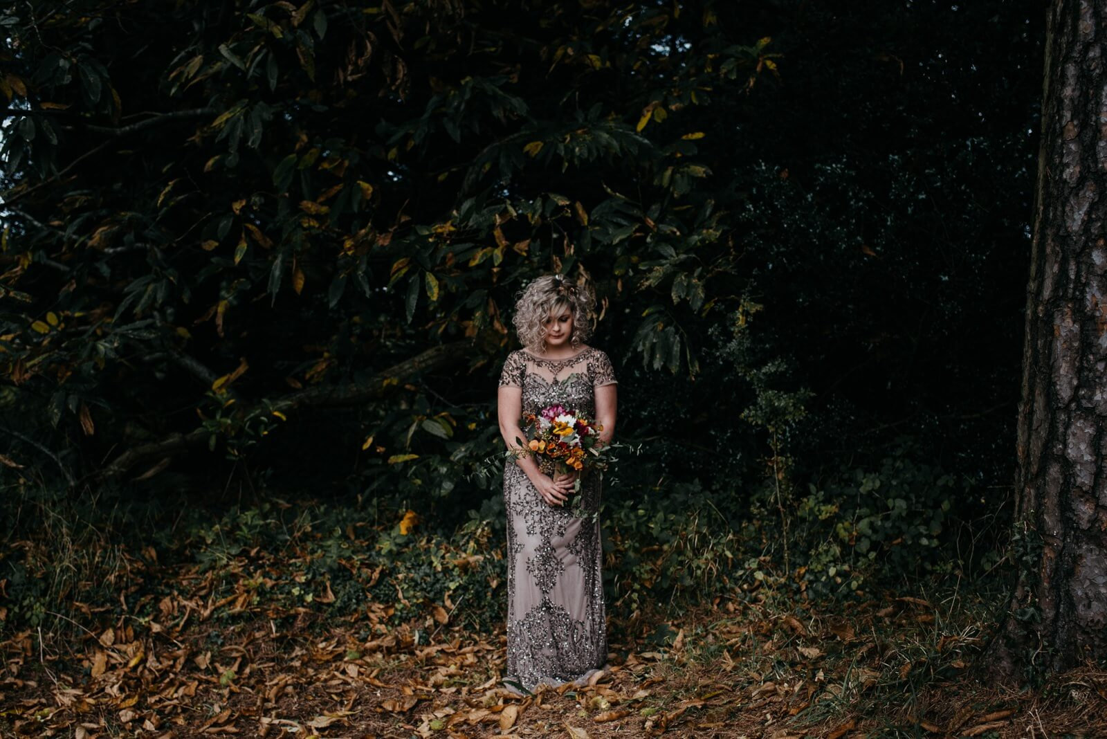 Alternative autumn bride wearing sequinned phase eight gown and holding handed bouquet featuring yellow, pink and white flowers in woodland with autumn golden leaves on the woodland floor