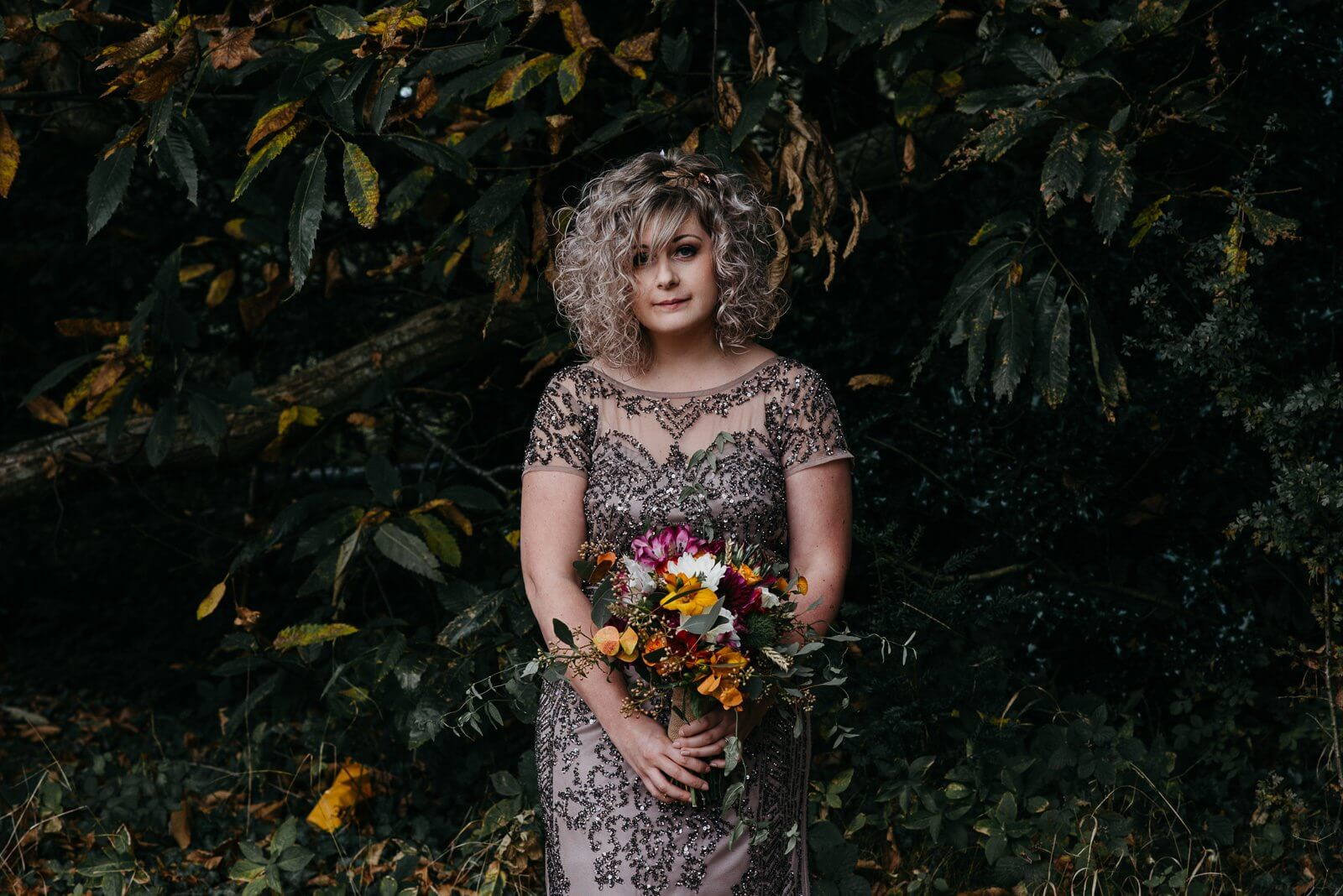 Alternative autumn bride wearing sequinned phase eight gown and holding handed bouquet featuring yellow, pink and white flowers