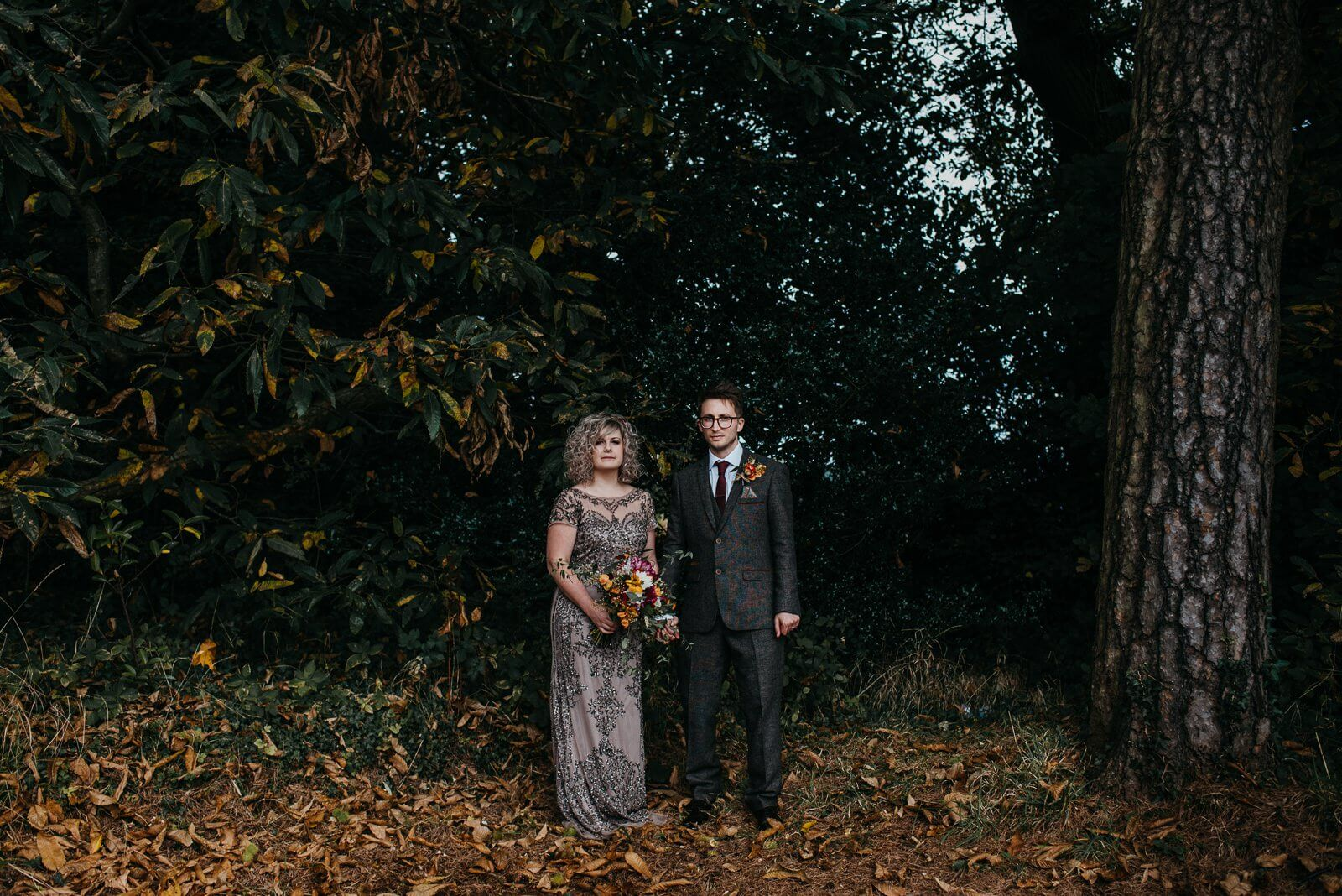 Moody portrait of bride and groom standing in woodland with autumn leaves of the floor at cardiff wedding