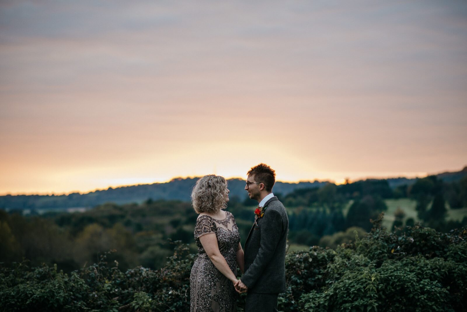 Cardiff Bride and Groom portrait infront of vast green landscape and autumn red sky sunset at golden hour