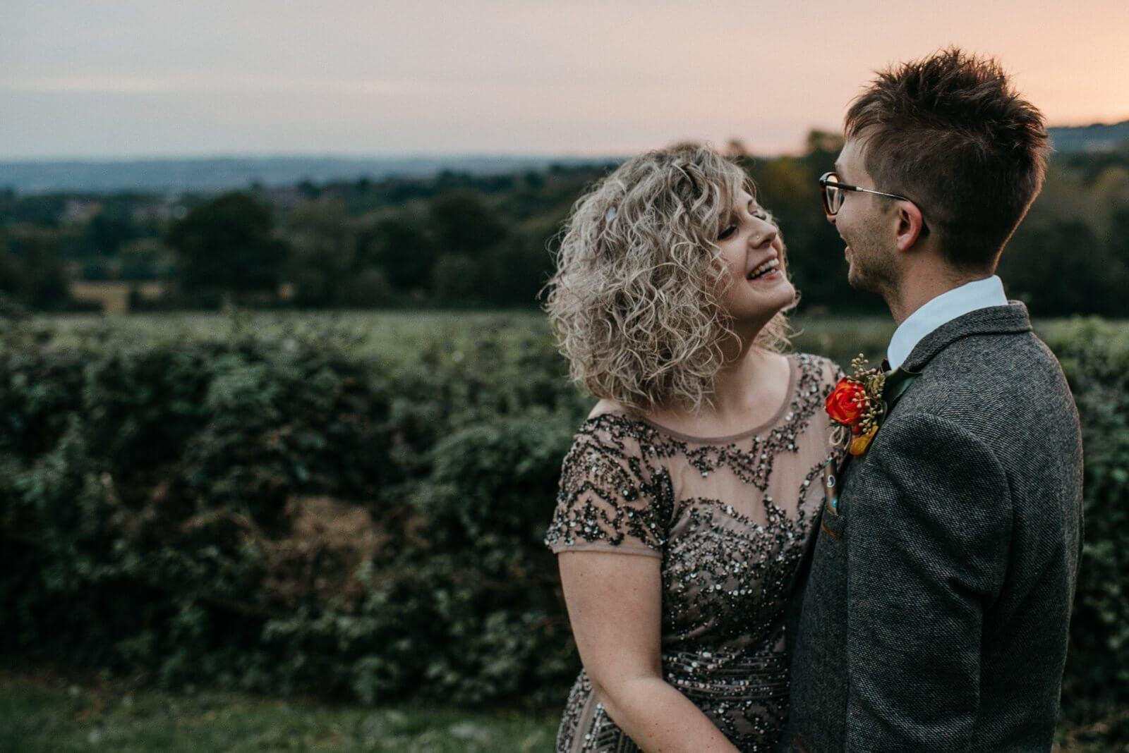 Bride wearing a sequin embellished gown smiling at her groom infront of rural landscape and autumn sunset at Ty Mawr, Cardiff