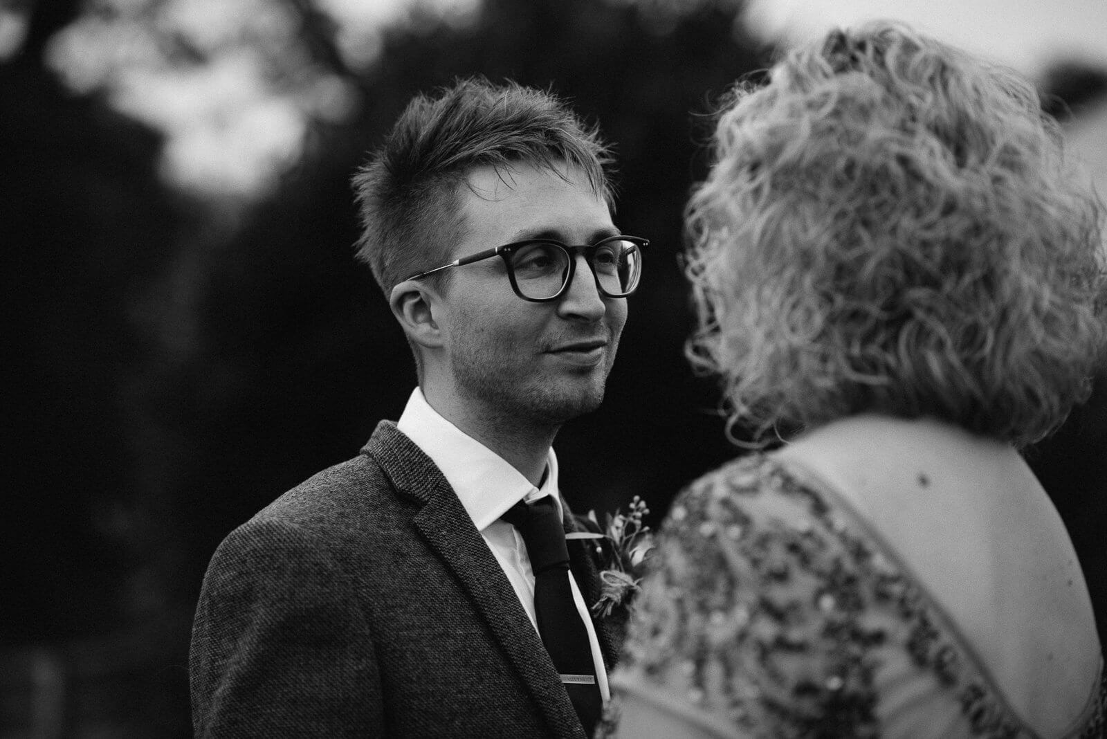 Black and white portrait of groom wearing glasses looking lovingly at his bride at their Cardiff wedding