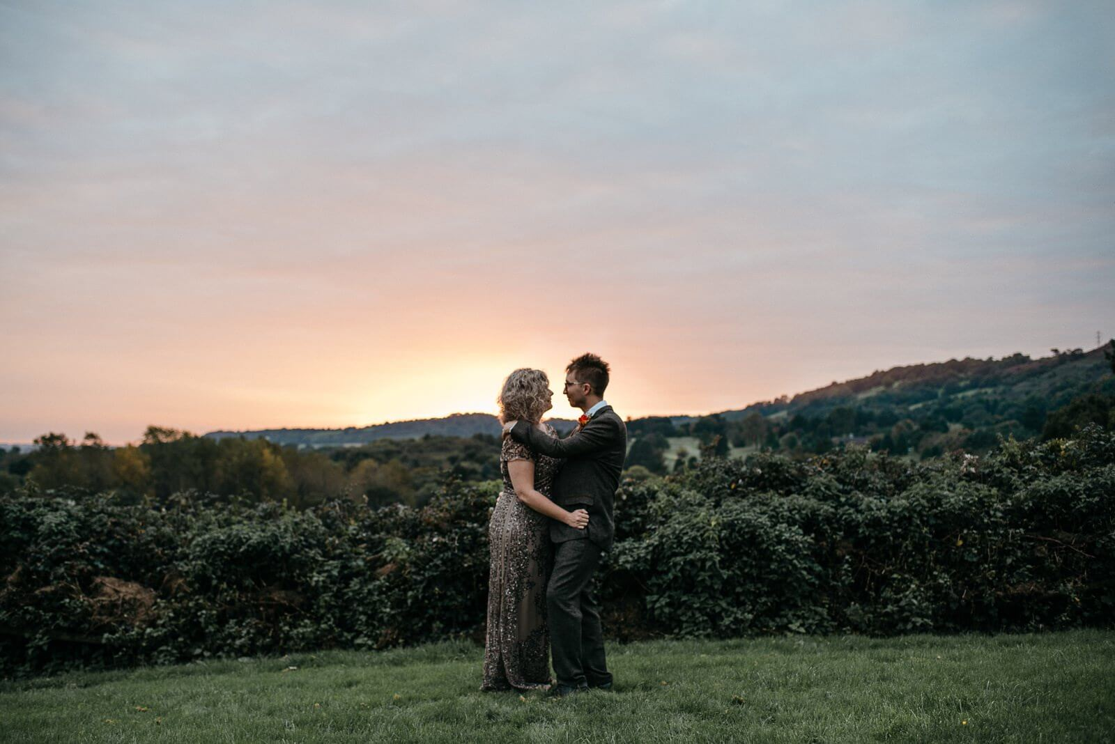 Bride and Groom embrace infront of Cardiff landscape and autumn sunset at Ty Mawr