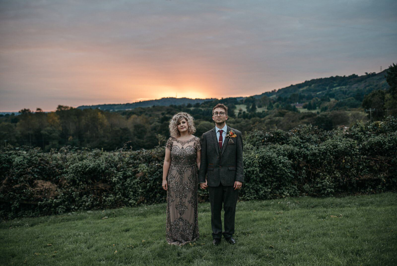 Bride and Groom in alternative couple portrait infant of Cardiff landscape and autumn sunset at Ty Mawr