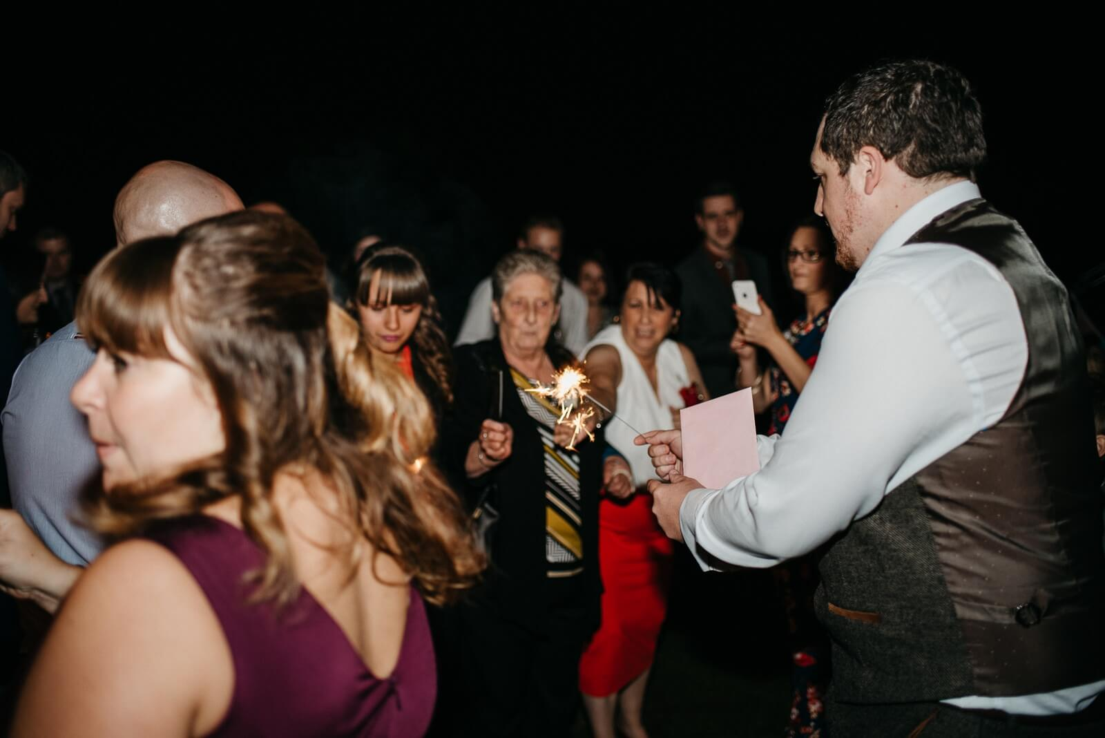 Guests lighting sparklers at Autumn alternative wedding in Cardiff