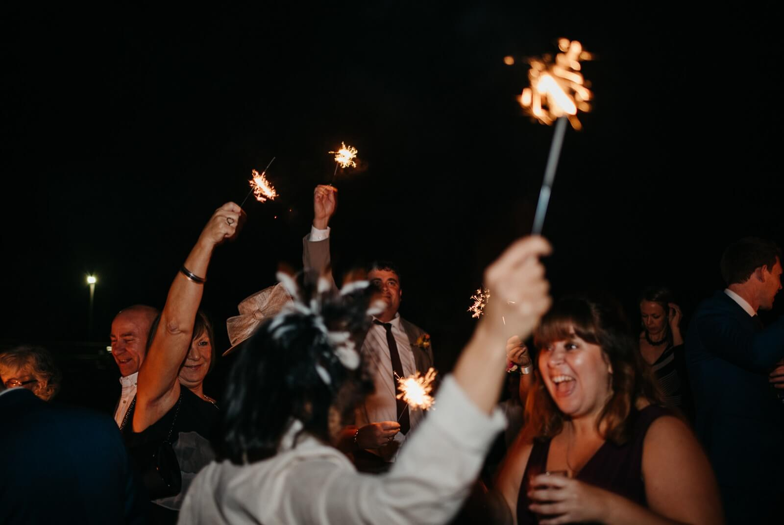 Wedding guests having fun with sparklers at autumn wedding at Ty Mawr, Cardiff
