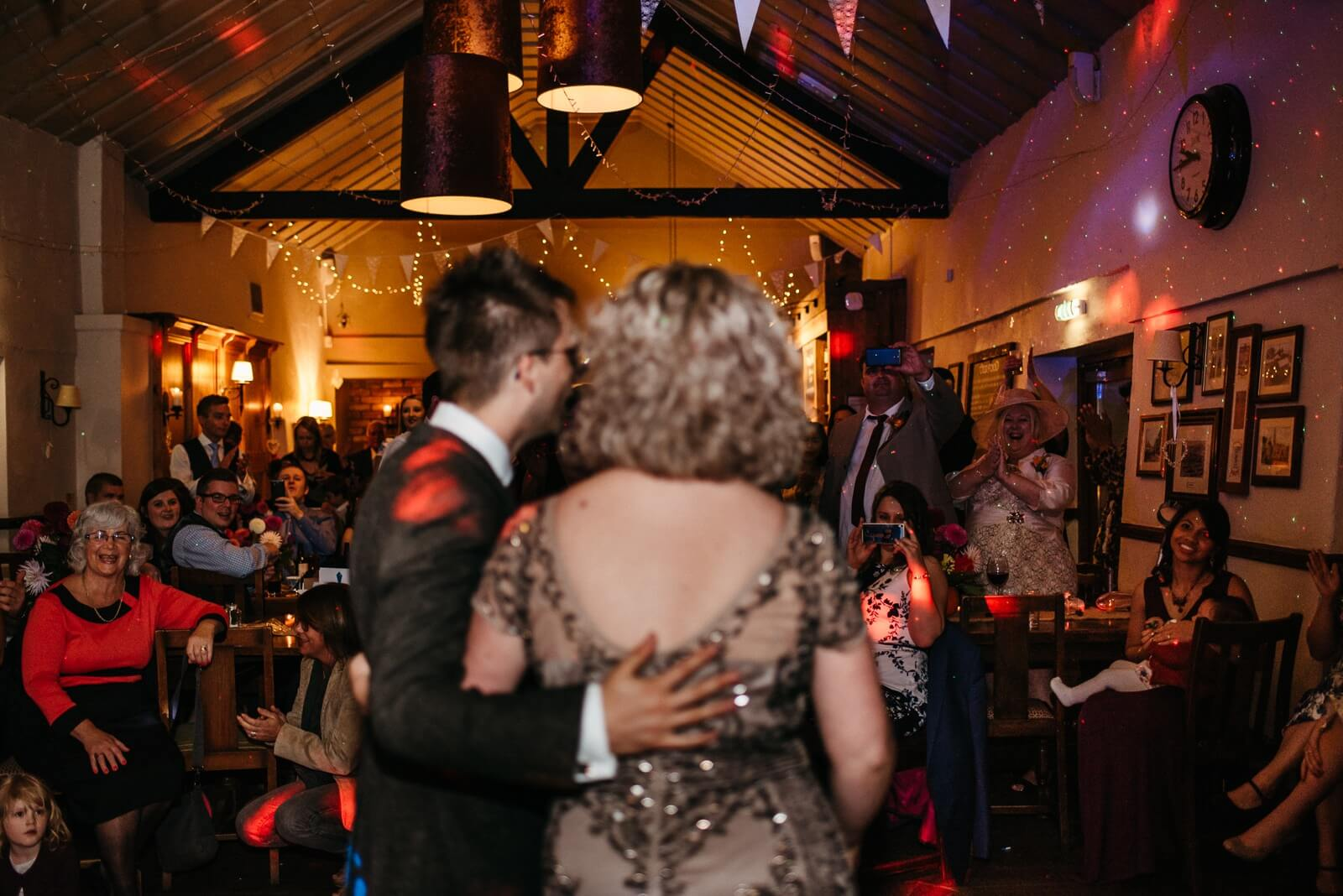 Bride and room inviting guests onto the dance floor in an old barn venue in Cardiff
