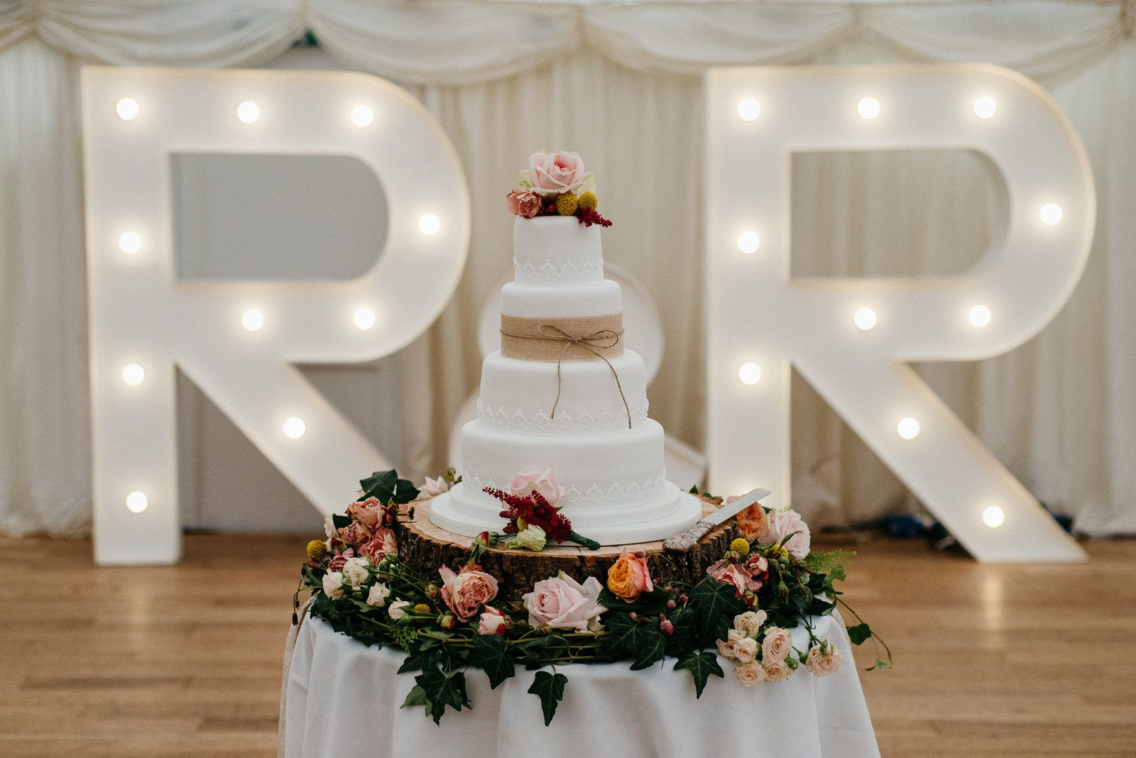 A white iced wedding cake adored with pale pink, peach and yellow flowers and lashings of foliage.