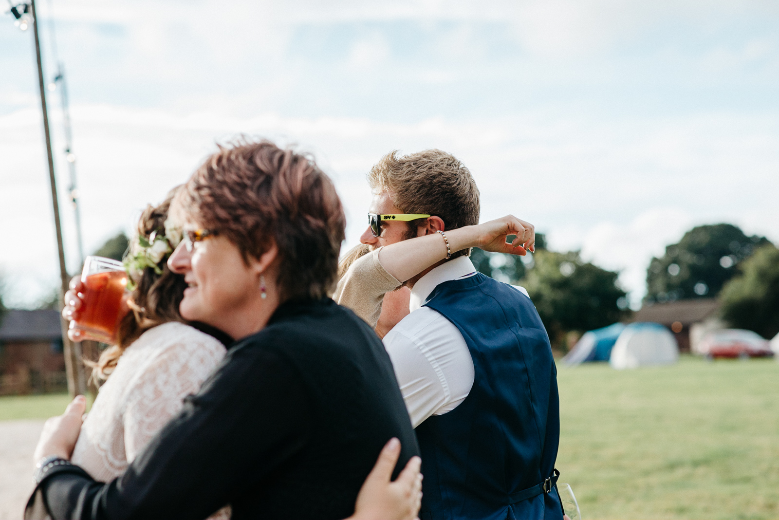 photograph of family hugging after bride and groom included friends on the wedding invitation list