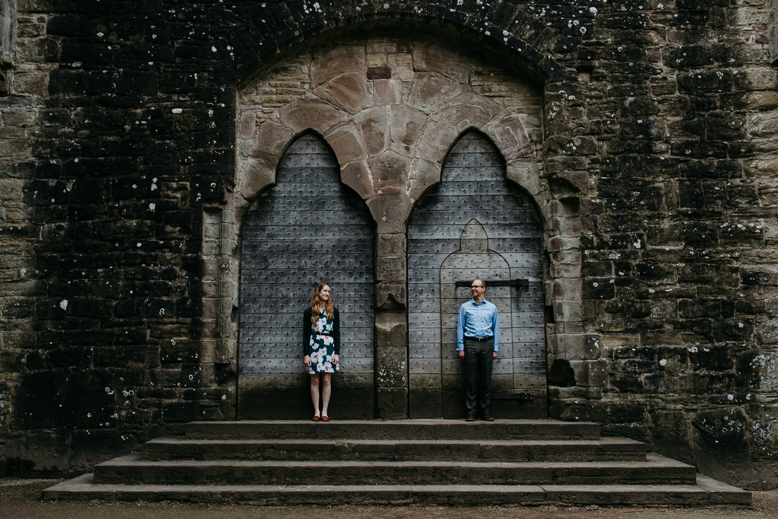Couple standing infront of huge doors inside Tintern Abbey during their per-wedding shoot