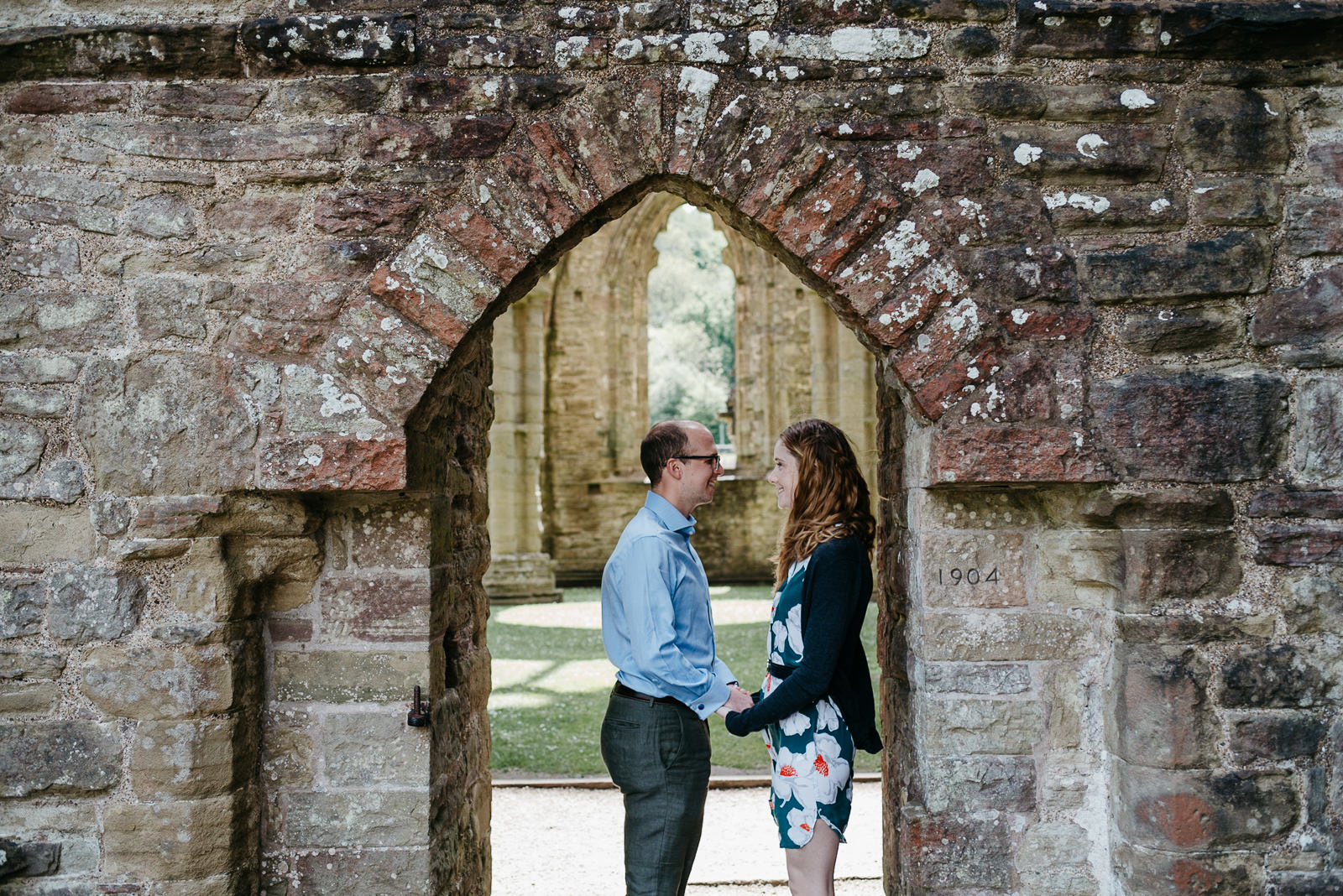 Bride and groom standing under arched doorway at Tintern Abbey