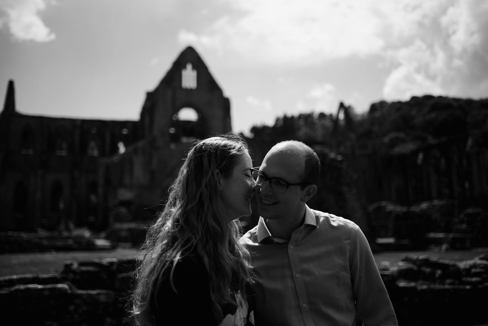 moody black and white photograph of couple in front of Tintern Abbey