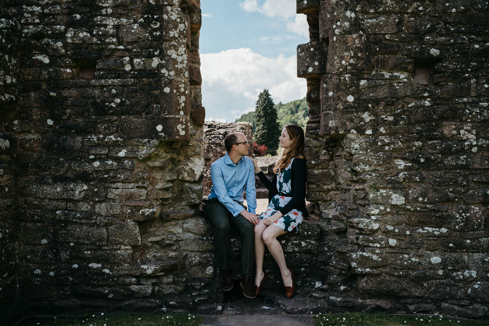 Bride & groom relaxing on castle ruins at Tintern