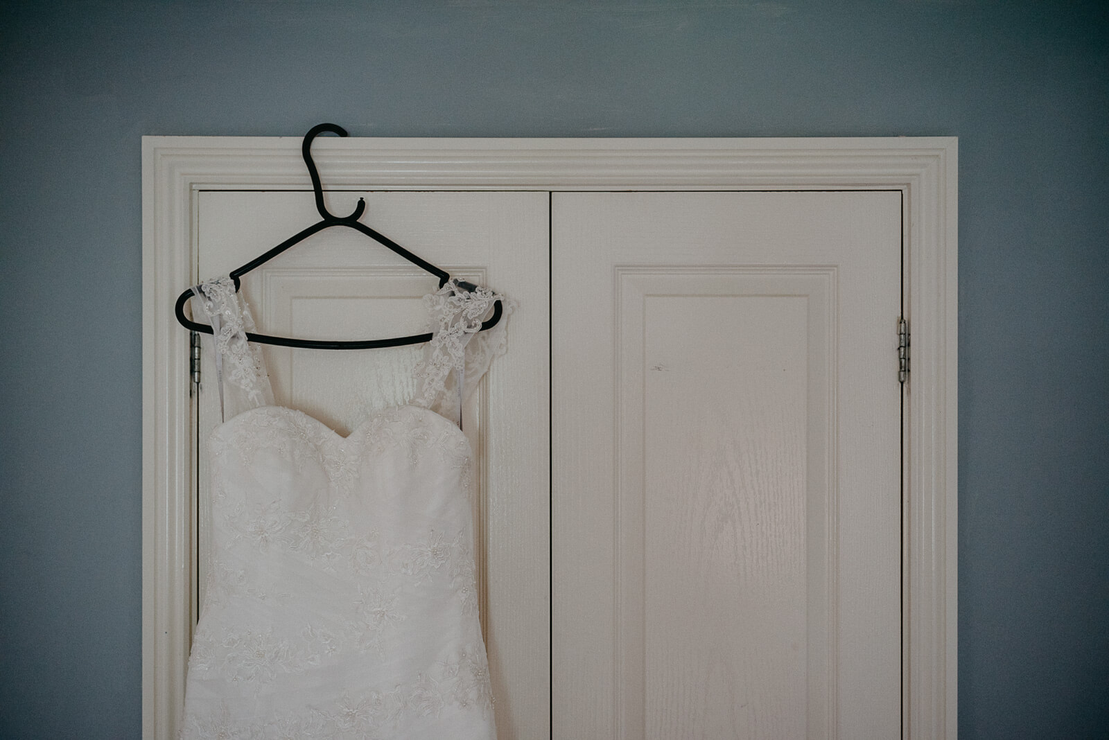 brides dress hanging in her bedroom