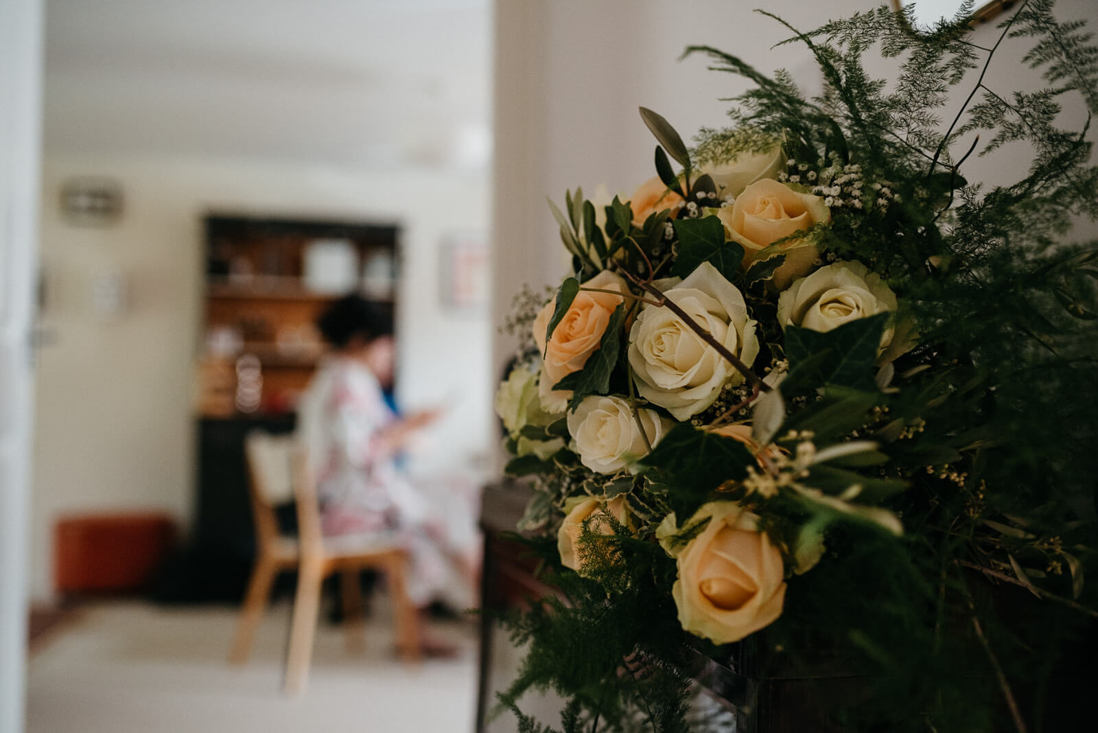 brides rustic bouquet of peach and cream roses, fern and foliage