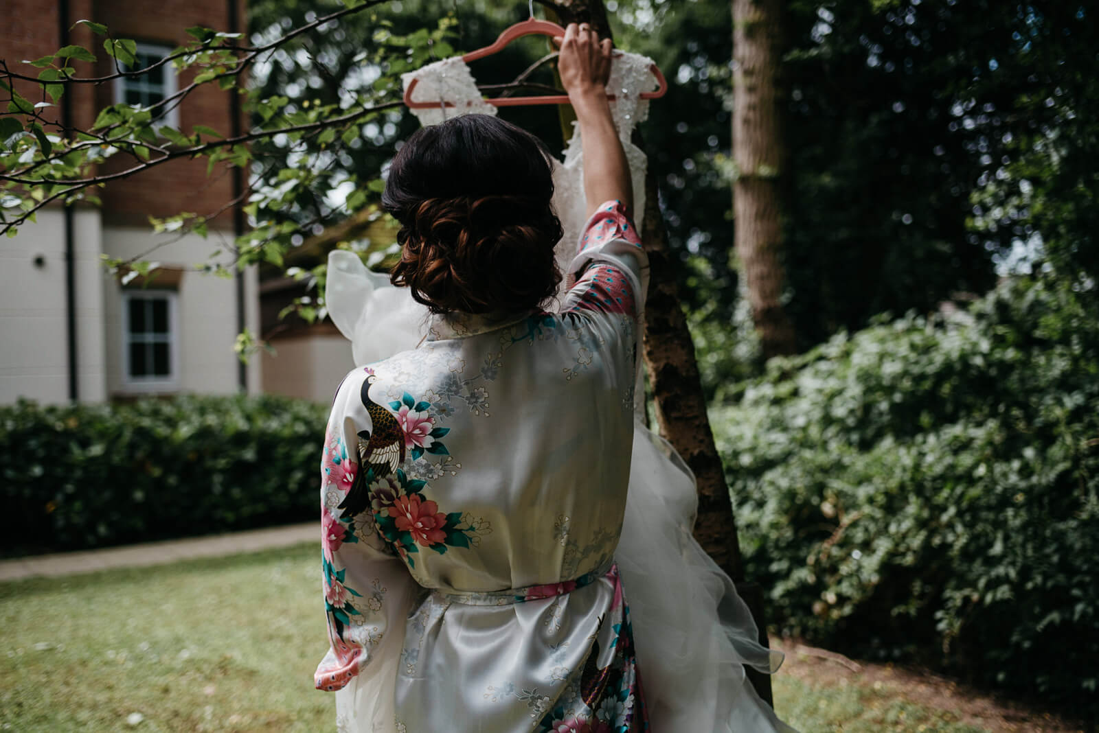 bride hanging her dress in the garden for rustic detail photographs