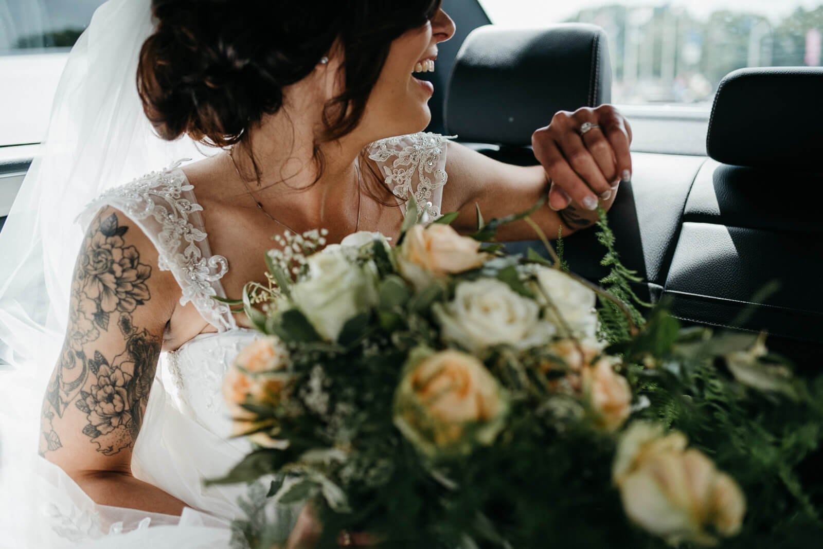 bride laughing when she sees her groom waiting for her at their cardiff wedding venue
