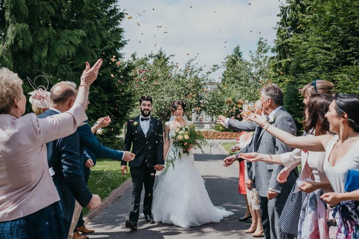 bride and groom walk though confetti after their Cardiff Registry Office wedding in South Wales