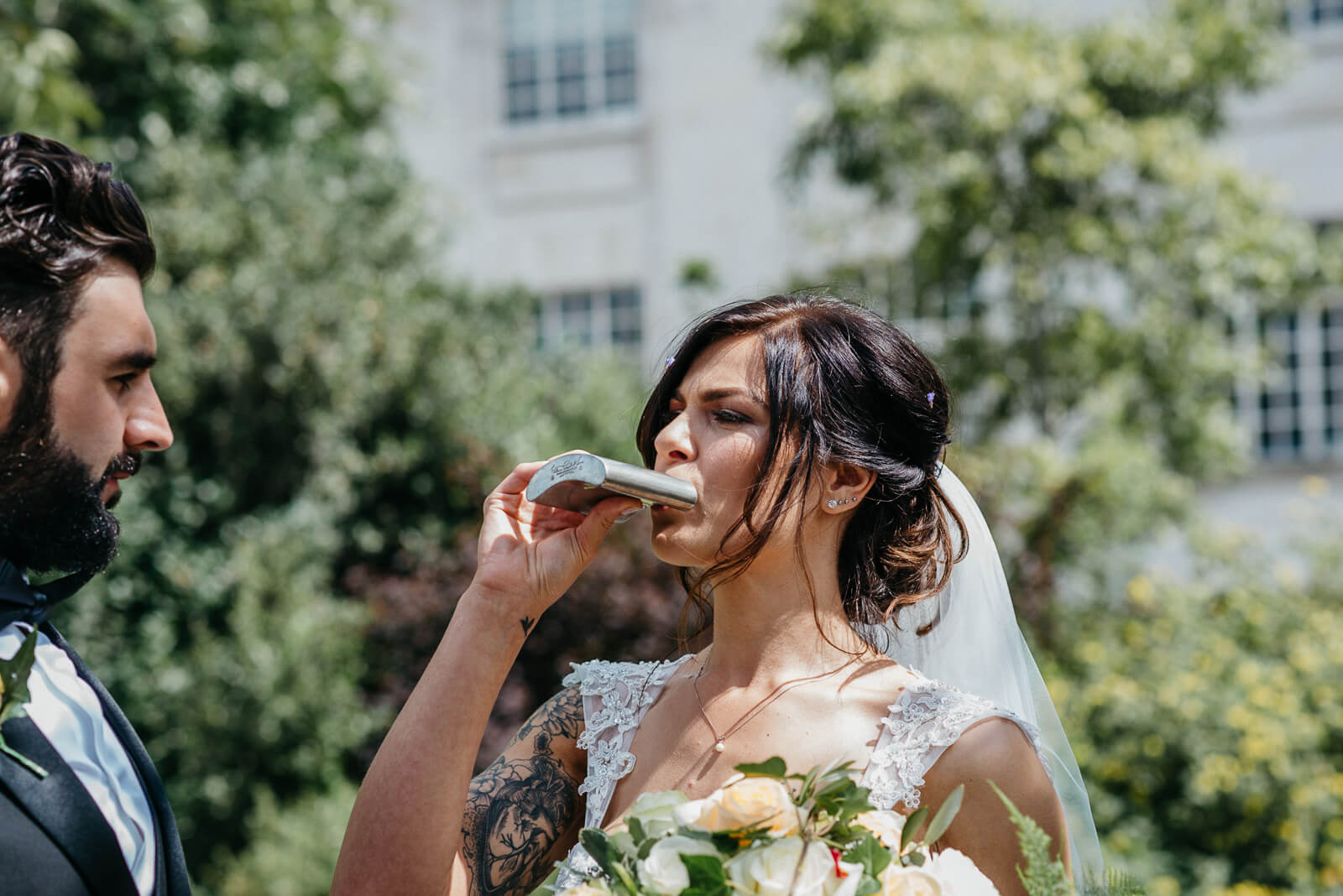 bride taking a swing from her new husbands hipflask following wedding ceremony