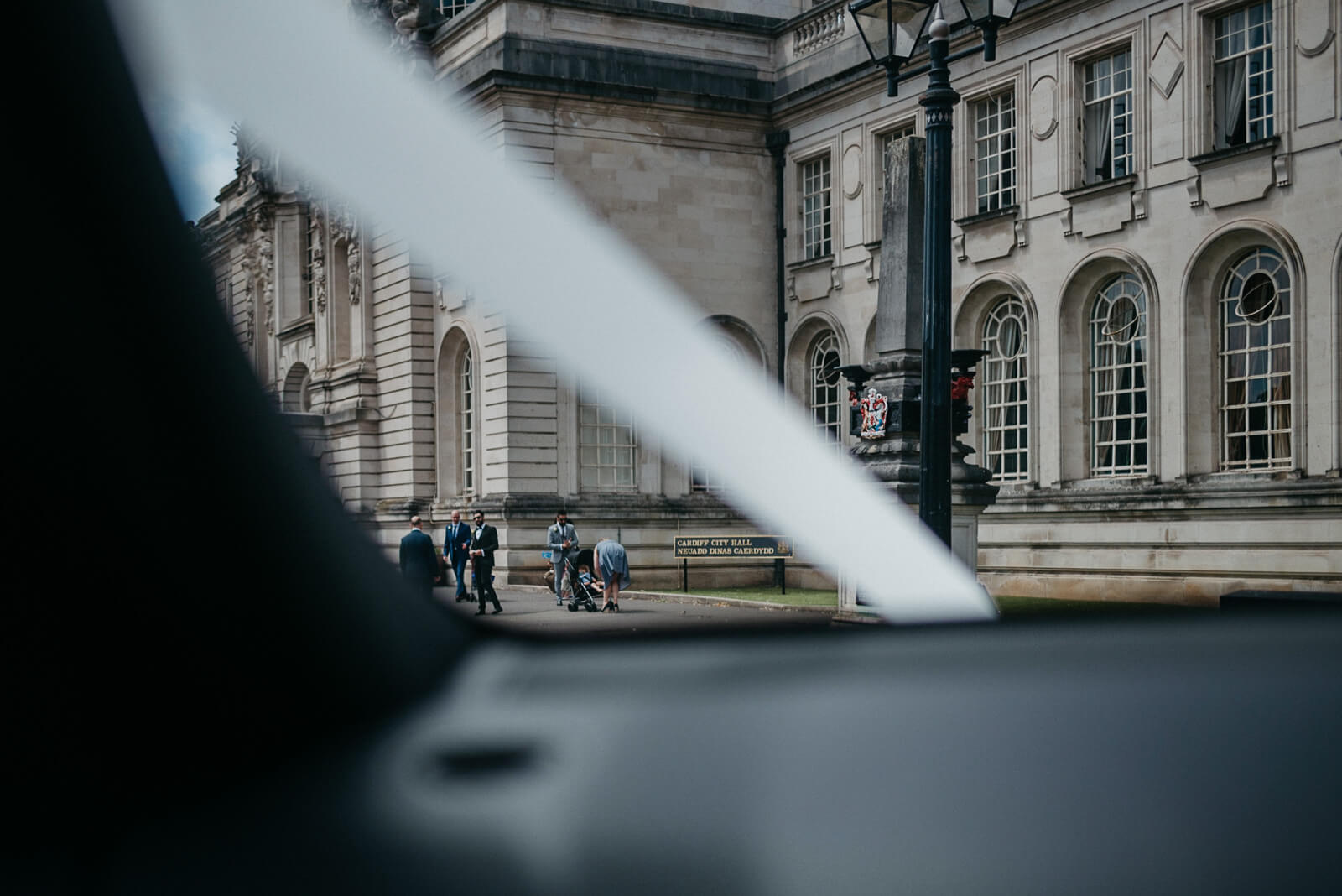groom in distance as wedding car arrives at city hall