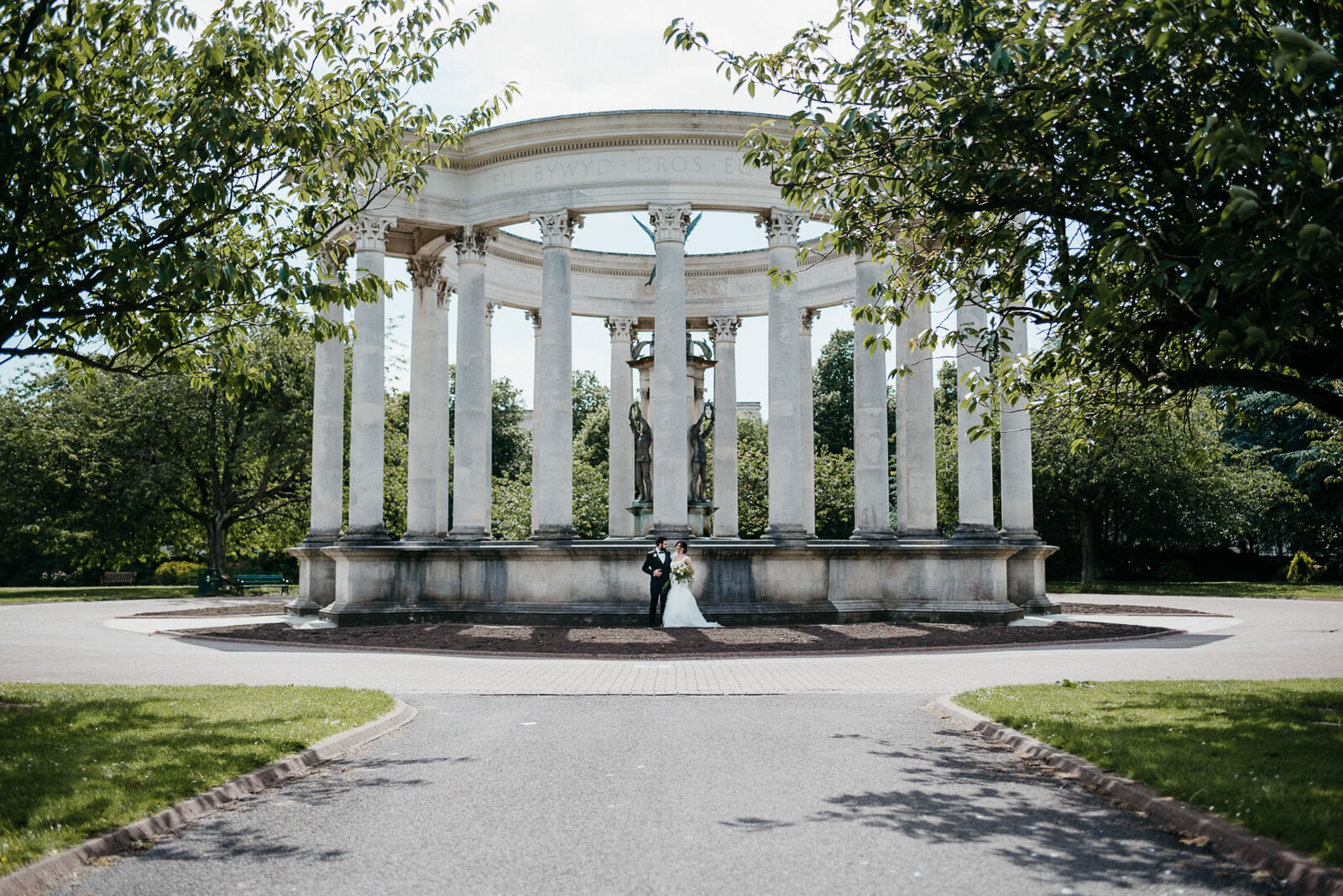 bride and groom stop by war memorial in city park